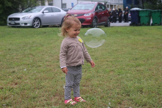 Selina Harris, 2, interacts with a bubble Saturday at a Rise for Climate event in the town of Poughkeepsie. Her mother, Cornelia, said she wants to work to improve the world for her daughter.