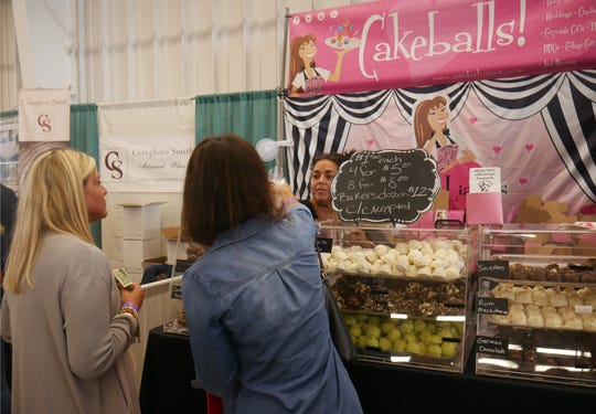 Heather Bragg (left) and Alicia Paonessa buy cake balls at Auntie Liana's Baked With Love stand at the Hudson Valley Wine & Food Fest on Sept. 8, 2018.