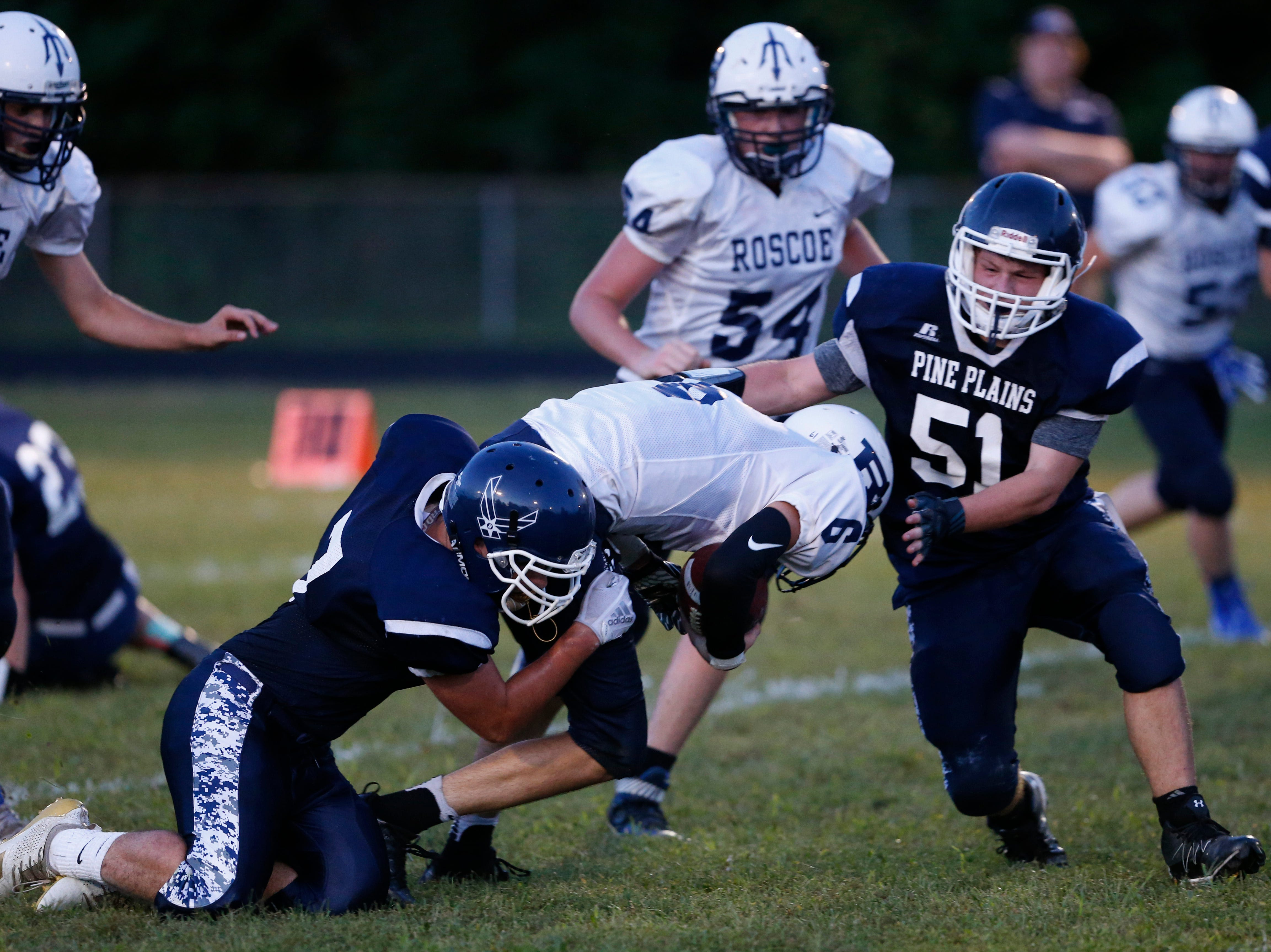 Roscoe's Erick Hill attempts to break free from Pine Plains', from left, Evan Proper and Bryce Stracher during Friday's game at Stissing Mountain High School on September 7, 2018.