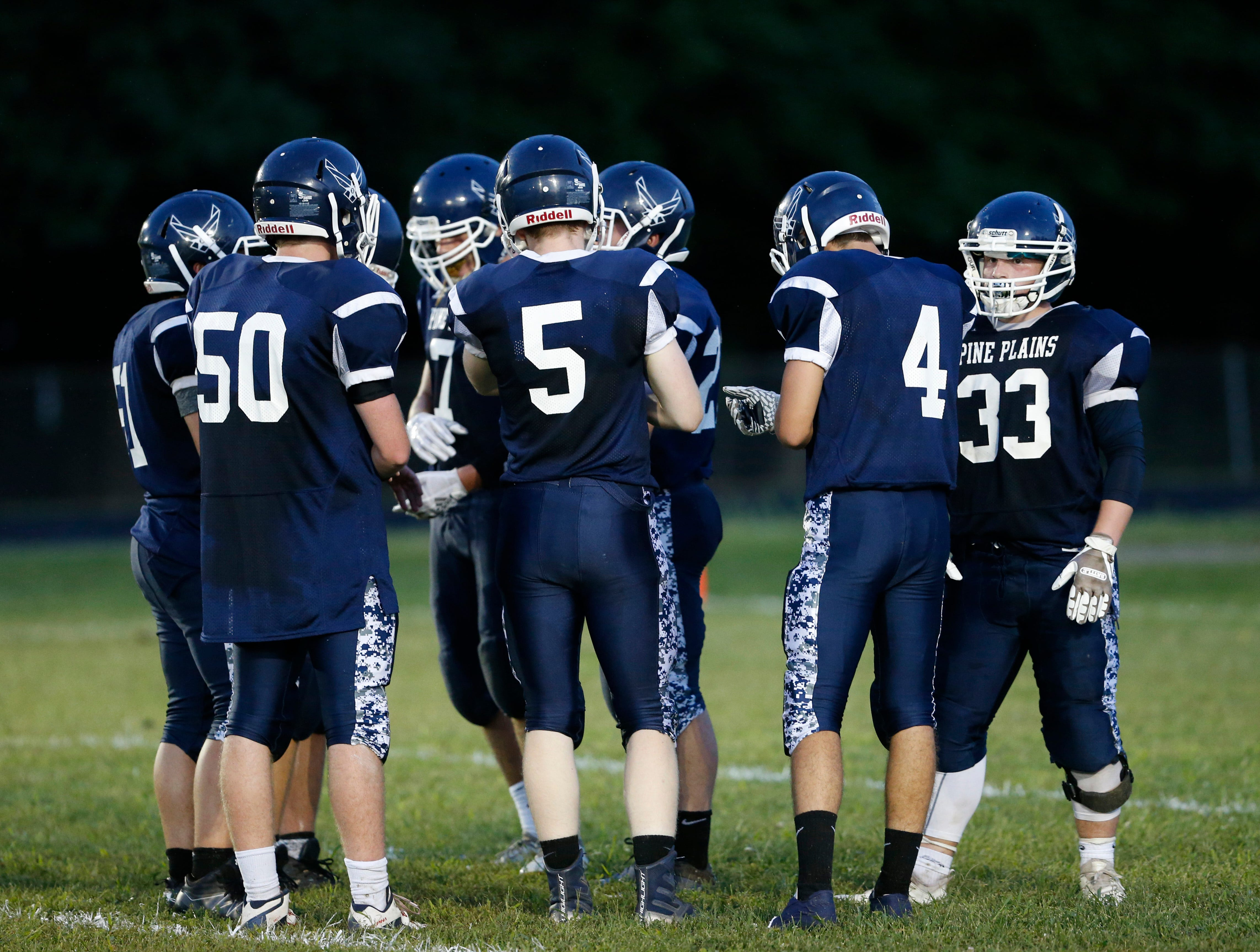 The Pine Plains offense huddles before running a play during its eight-man football game against Roscoe on Friday.