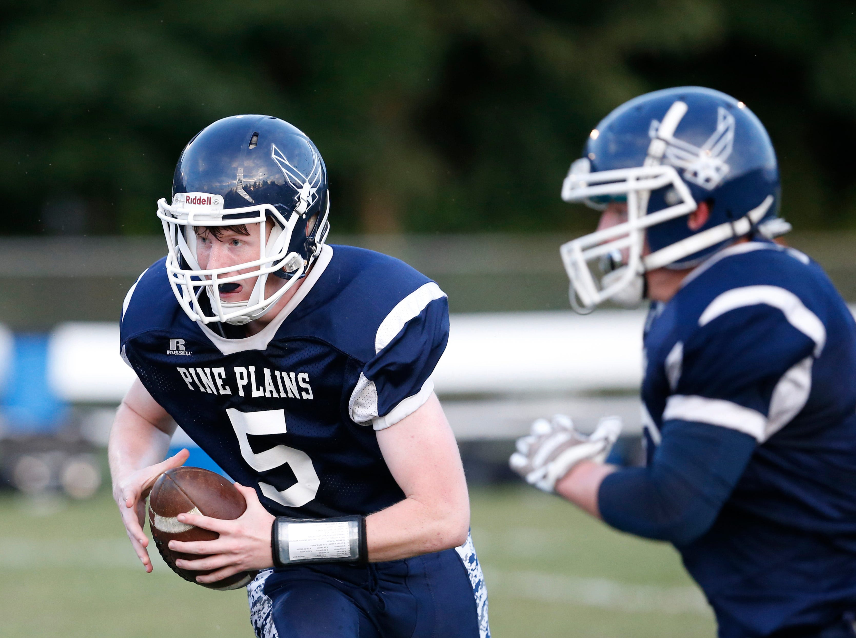 Pine Plains' Andrew Holsopple carries the ball as Kyle Stracher covers his path during Friday's home gam versus Roscoe on September 7, 2018.