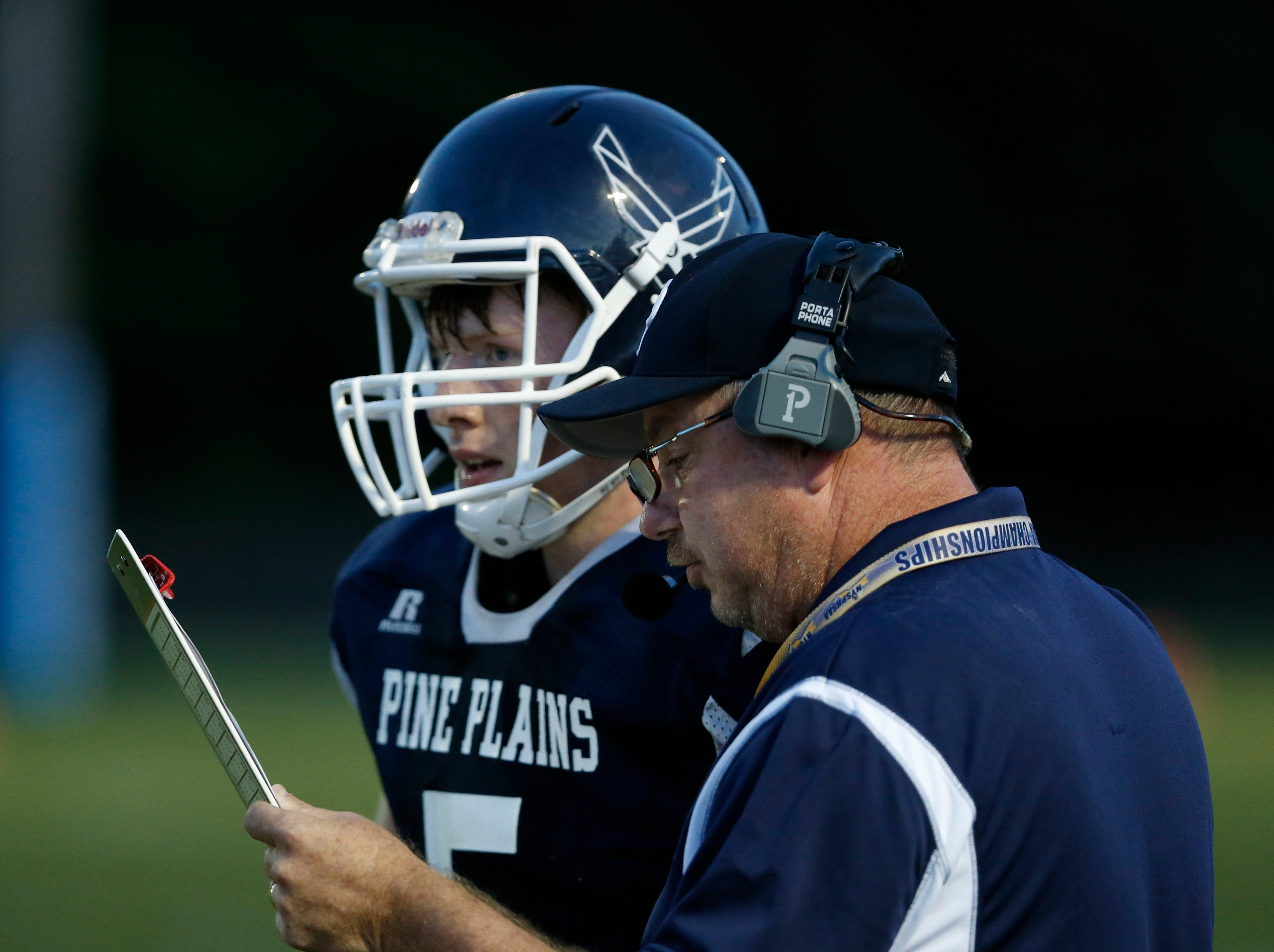 Pine Plains' head coach Rob Scott goes over a play with quarterback Andrew Holsopple during Friday's game versus Roscoe at Stissing Mountain High School on September 7, 2018.