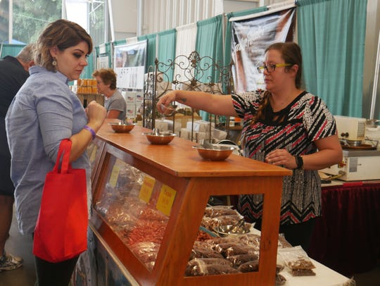 Lysette Seedorf of Beacon gets a sample of candied nuts from Desiree Pease at the Old Country Style Bavarian Nuts stand, one of many vendors at the Hudson Valley Wine & Food Fest, on Sept. 8, 2018.