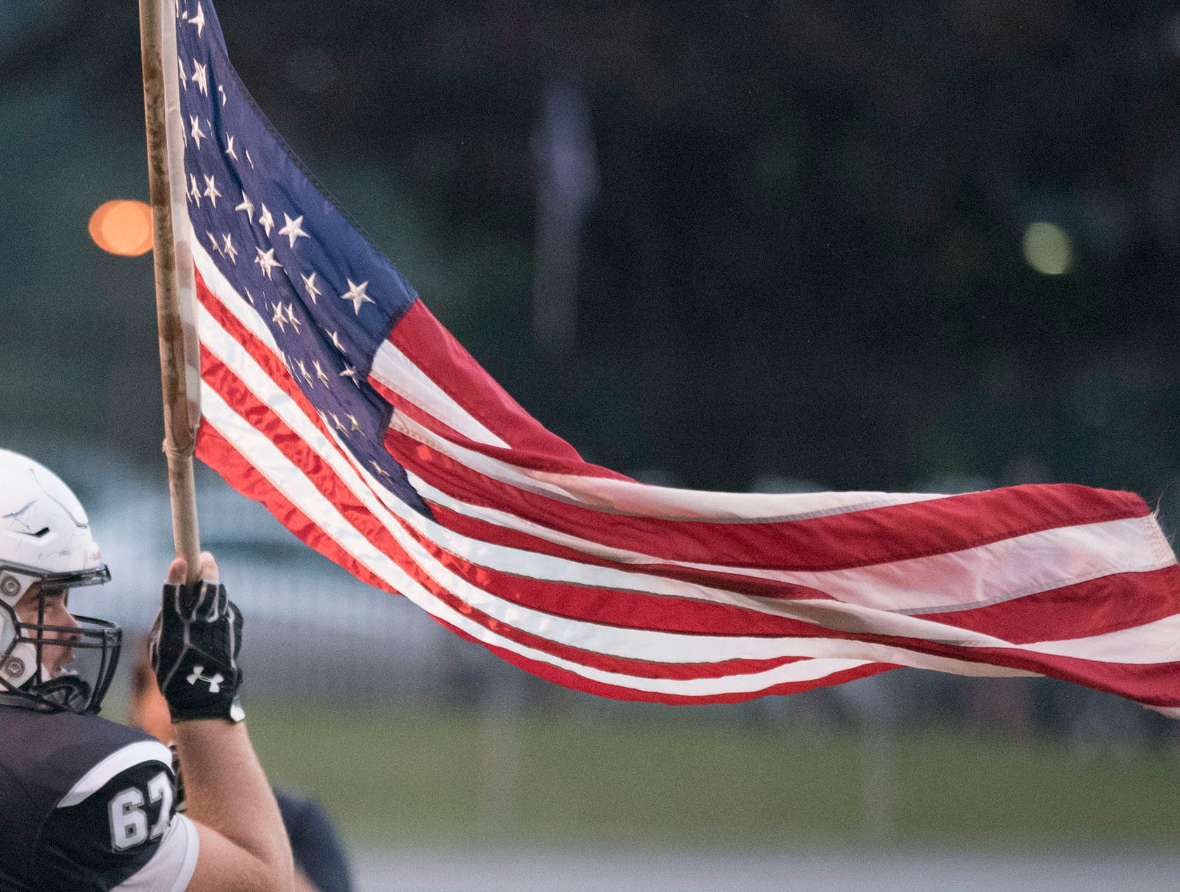 Chambersburg's Brock Harmon carries the U.S. flag for the Trojans. Chambersburg defeated Red Lion 28-19 in PIAA football on Friday, Sept. 7, 2018.