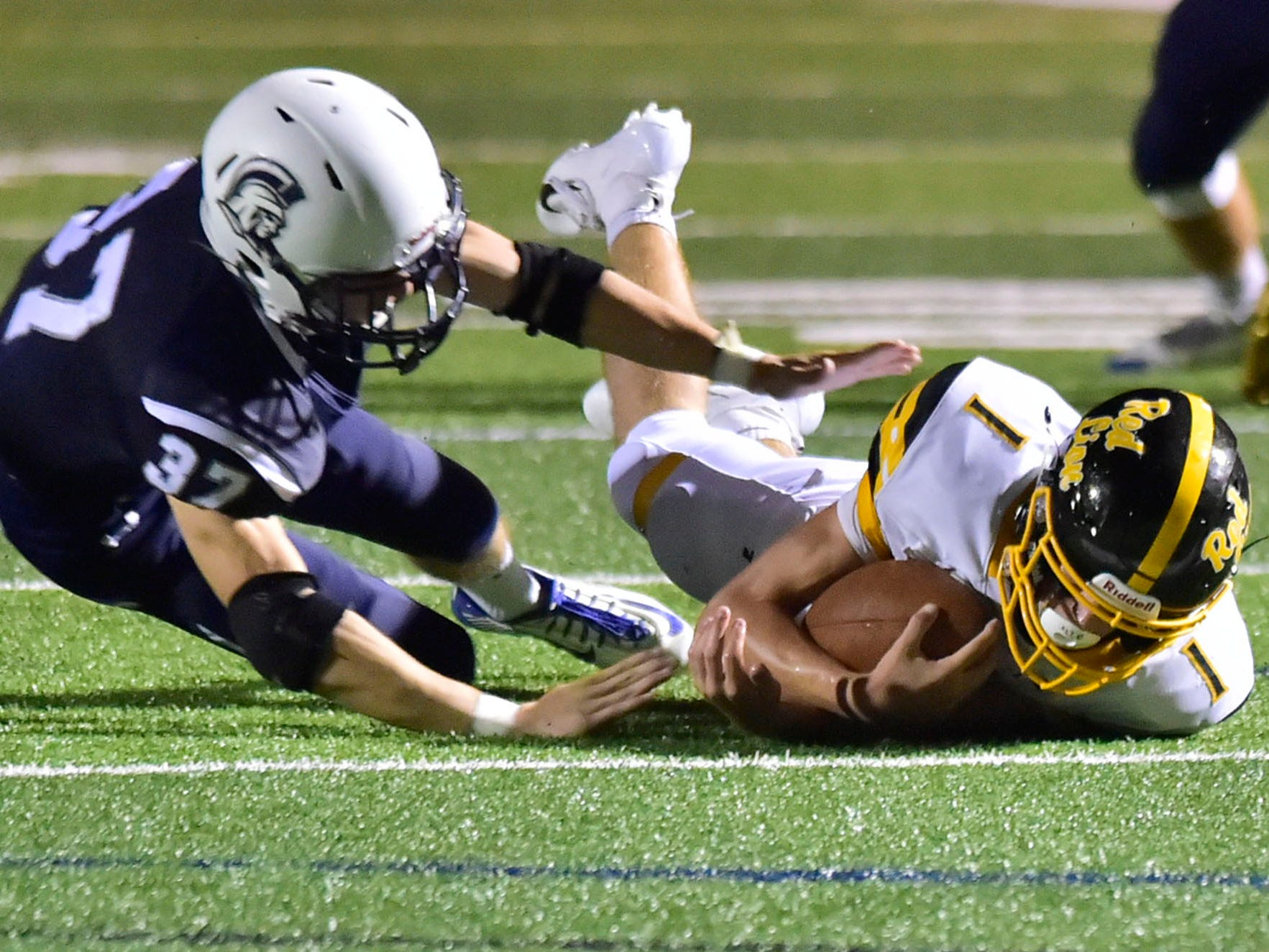 Red Lion's Randy Fizer (1) loses his footing and is tackled by Chambersburg's Levi Mixell. Chambersburg defeated Red Lion 28-19 in PIAA football on Friday, Sept. 7, 2018.