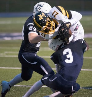 Red Lion's Davante Dennis (21) is tackled by Chambersburg's Tyeshawn Worrell (3) and Andrew Shetter. Chambersburg defeated Red Lion 28-19 in PIAA football on Friday, Sept. 7, 2018.