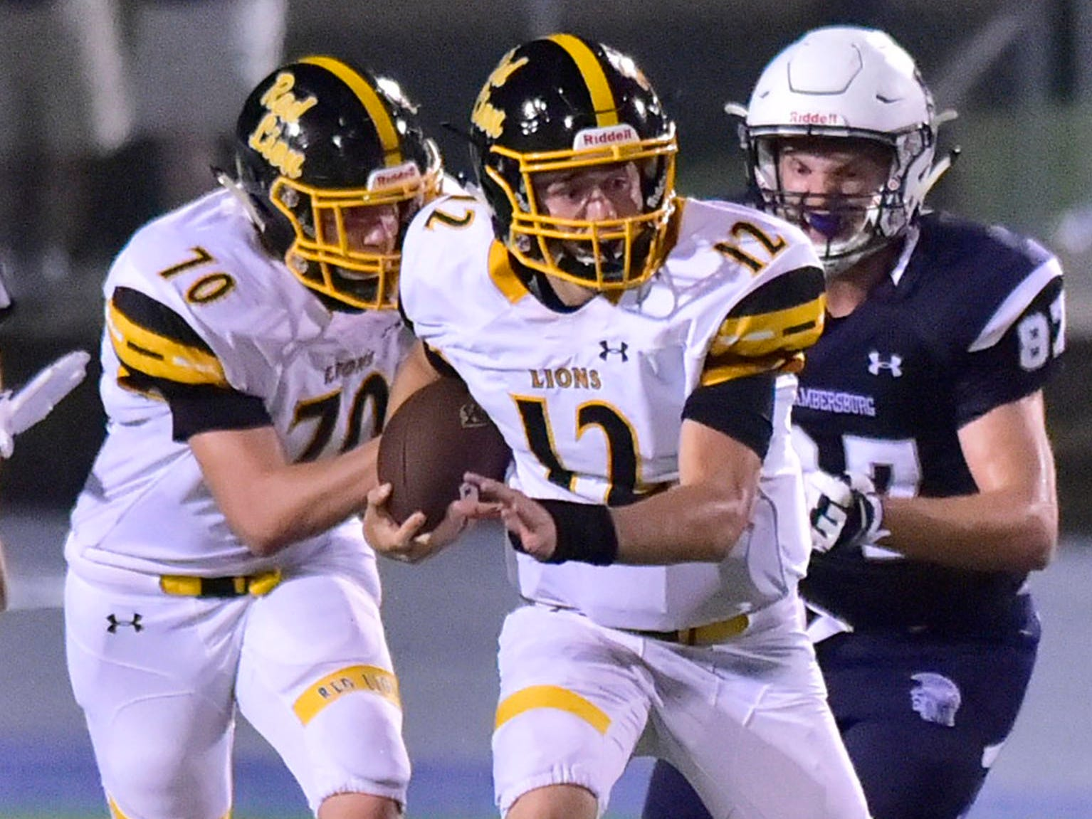 QB Zach Mentzer (12) is on the run for Red Lion as Chambersburg's Bryce Diller (87) pursues. Chambersburg defeated Red Lion 28-19 in PIAA football on Friday, Sept. 7, 2018.