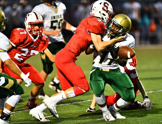Susquehannock's Henry Rohlfs forces a fumble against York Catholic's punt returner Jabbar Sease during football action at Susquehannock High School in Glen Rock, Friday, Sept. 7, 2018. The game would be delayed at the half, due to lightning, with York Catholic up 7-3. Dawn J. Sagert photo