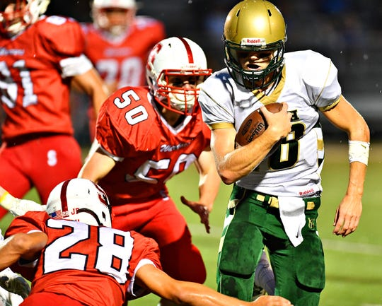 York Catholic quarterback Wes Burns looks for yardage against Susquehannock on Friday night. Burns and the Fighting Irish are off to a 3-0 start. Dawn  J. Sagert photo