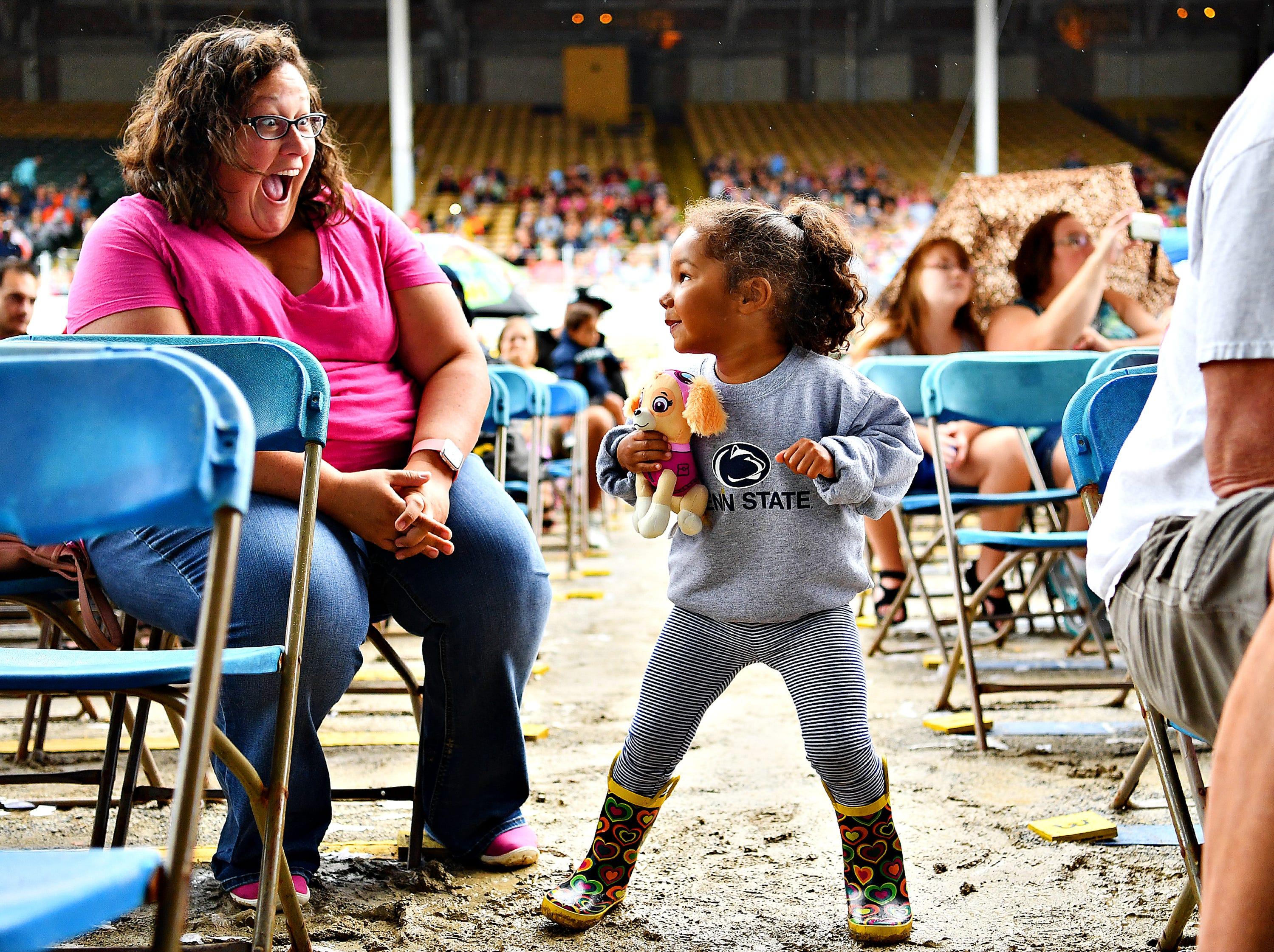 Julia Liddick, left, of York City, looks on as her daughter Averie Liddick, 2, dances during the early performance of Sesame Street Live at York Fair, Saturday, Sept. 8, 2018. Dawn J. Sagert photo