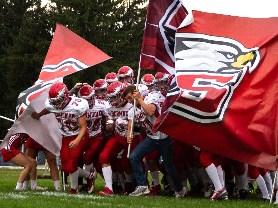 Bermudian Springs players break through their banner before Friday night's game against Shippensburg.