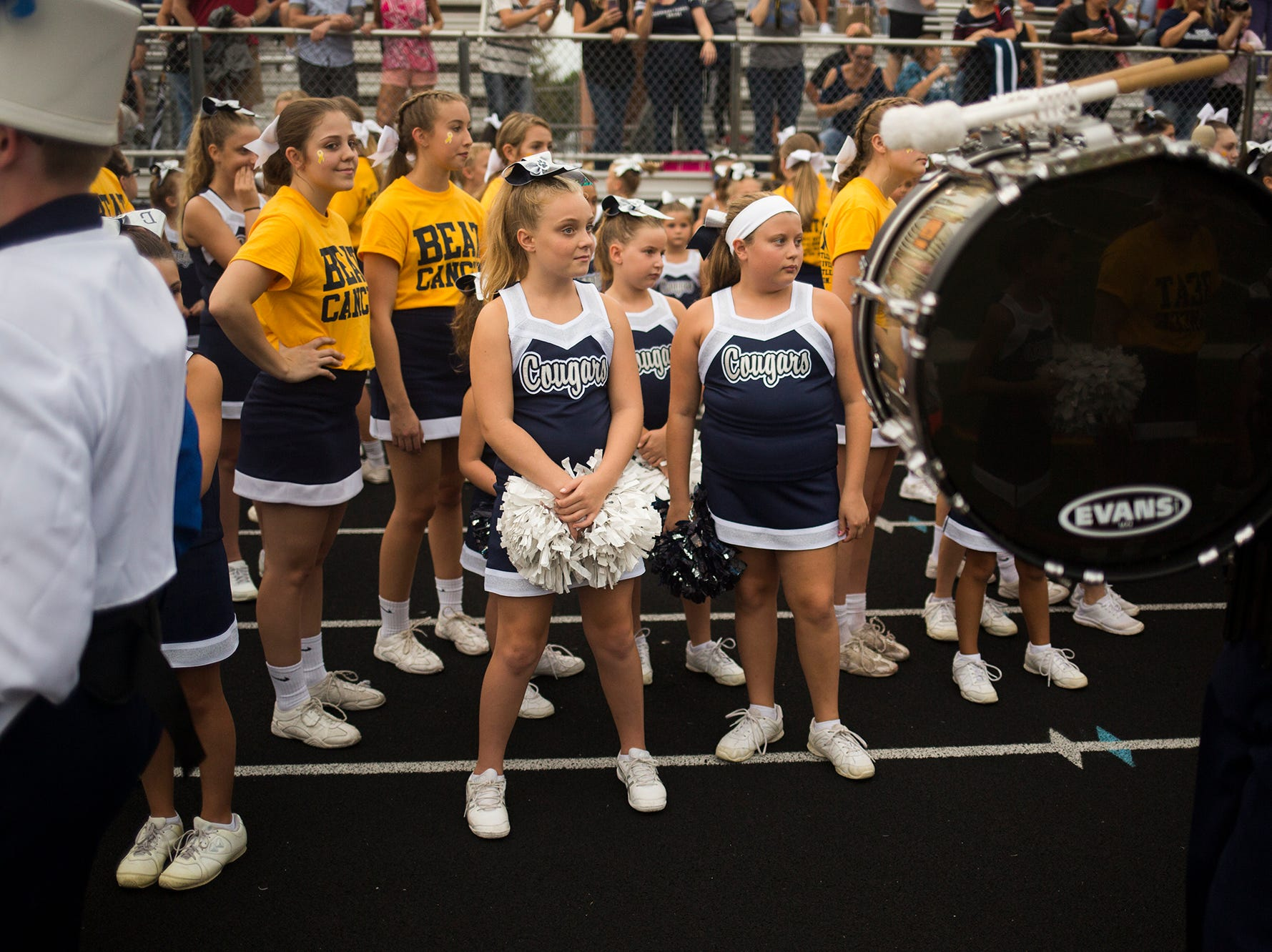 Dallastown Area High School cheerleaders stand with Dallastown youth cheerleaders as the school's marching band enters the stadium prior to the game. Dallastown defeats Penn Manor 42-7 in football at Dallastown Area High School in Dallastown, Friday, September 7, 2018.