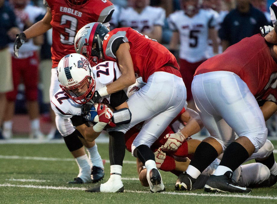 Red Land's Hayden Zechman (22) looks for more yardage as two Dover defensemen tackle him down, Friday, September 7, 2018. The Dover Eagles beat the Red Land Patriots, 35-13, at Dover High School.