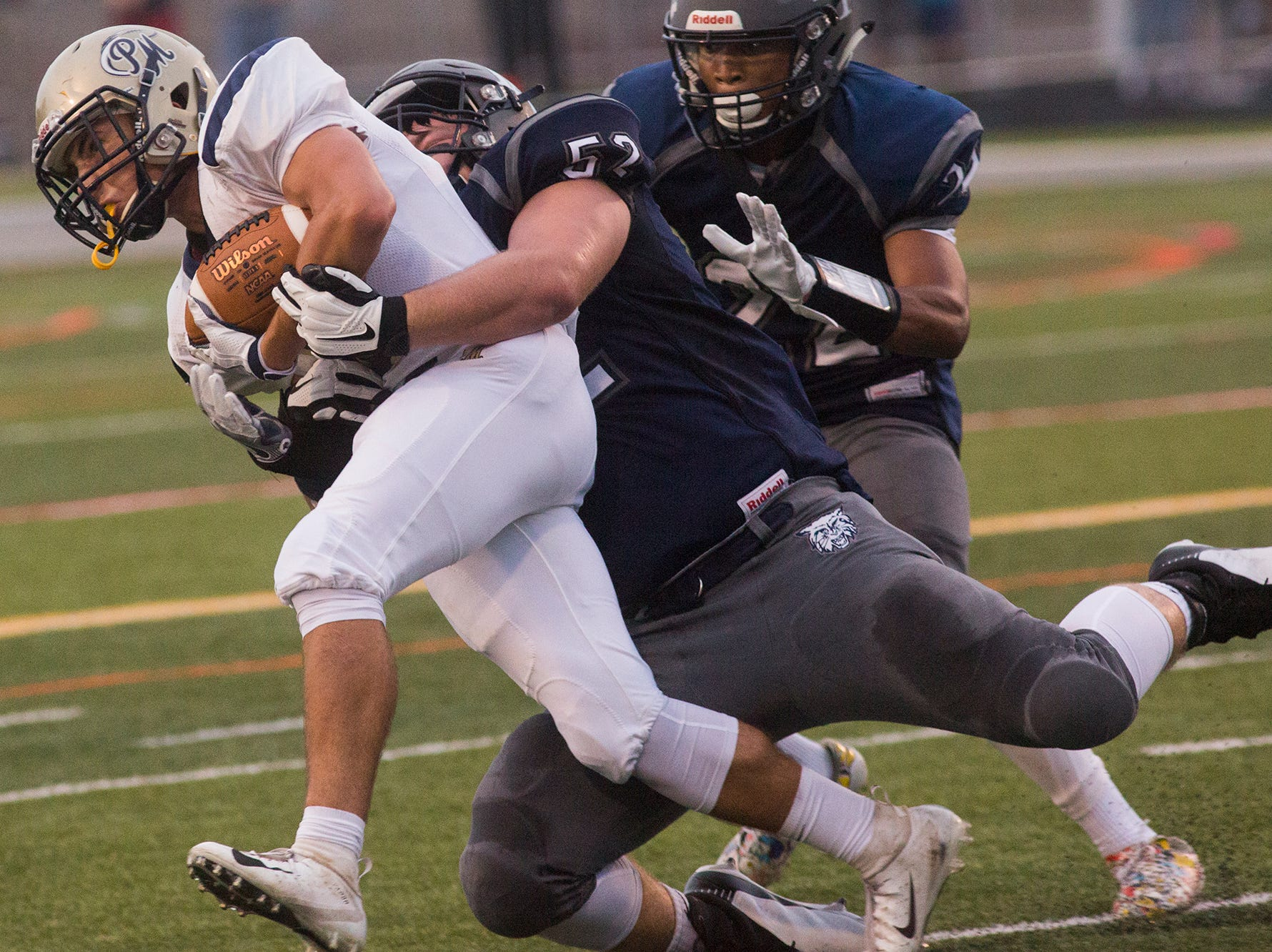 Dallastown's Lucas Skelley, center, tackles a Penn Manor ball carrier. Dallastown defeats Penn Manor 42-7 in football at Dallastown Area High School in Dallastown, Friday, September 7, 2018.