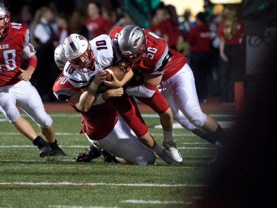 Dover's Jack Helsel (70) and Kameron Anderson (50) tackle Red Land quarterback Adam Cramer (10),