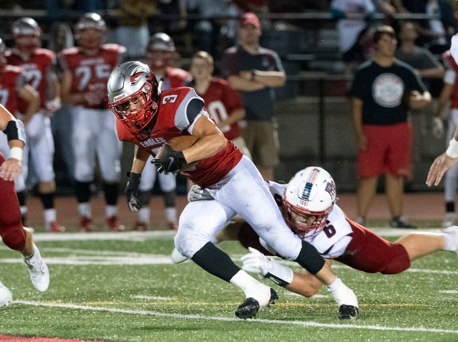 Dover's Derek Arevalo (3) runs the ball up the field as Red Land's Dylan Rodenhaber goes for the tackle, Friday, September 7, 2018. The Dover Eagles beat the Red Land Patriots, 35-13, at Dover High School.