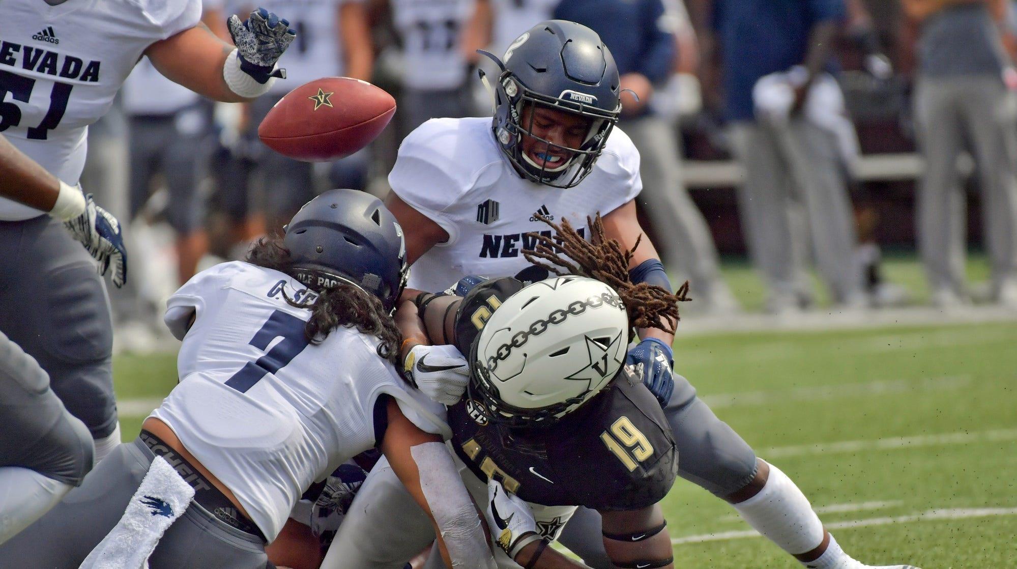 Vanderbilt wide receiver Chris Pierce (19) fumbles the ball against Nevada Wolf Pack linebacker Gabriel Sewell (7) during the first half at Vanderbilt Stadium.
