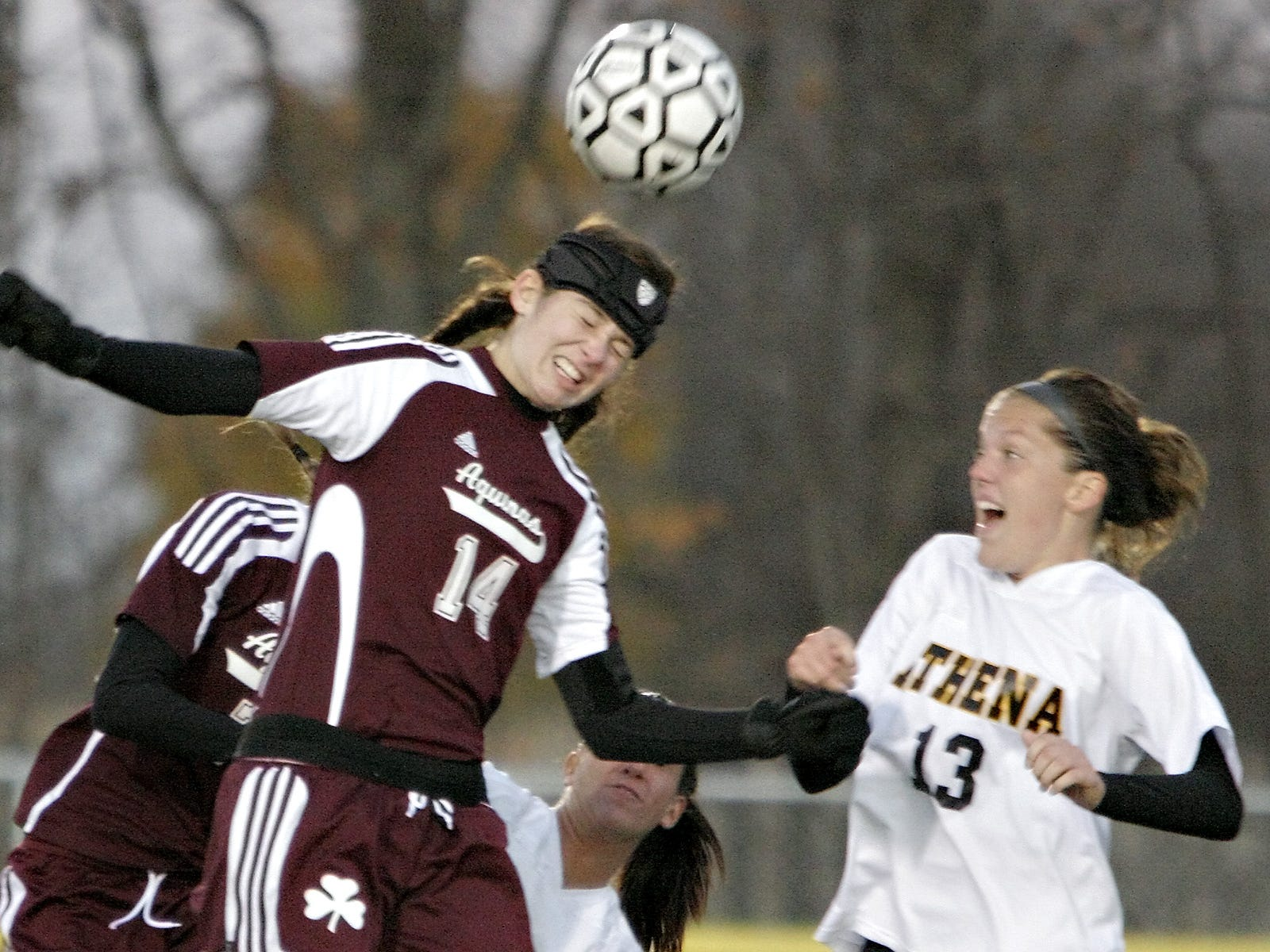 Aquinas' Olivia Guy heads the ball as Greece Athena's Katie Mibaum watches during the Class AA final at Caledonia-Mumford on Nov. 1, 2008.