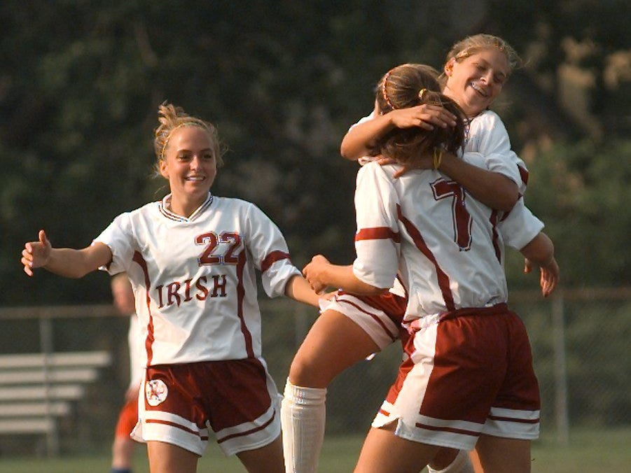 Aquinas teammates, Jacquie Lacek (top right) and Kathlen Wania (22) congratulate Lauren Mort (7) on her goal against Rush-Henrietta on Sept. 8, 1999.