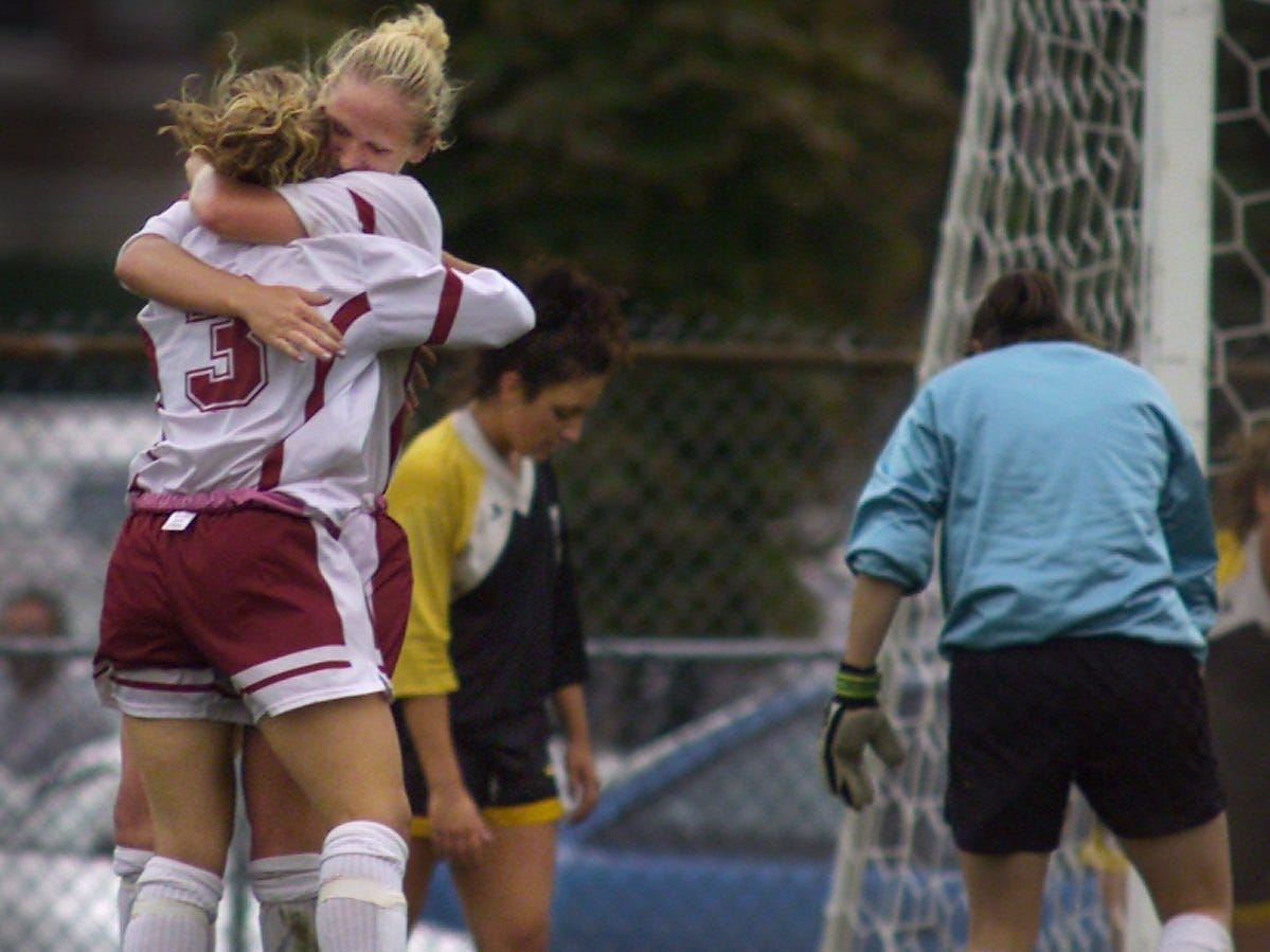 Lauren Popovich, left, and Lindsay Maleski celebrate Popovich's goal near a dejected trio of Greece Athena players during the second half of their game on Wednesday, Sept. 19, 2001 at Aquinas. The game finished in a 1-1 tie.