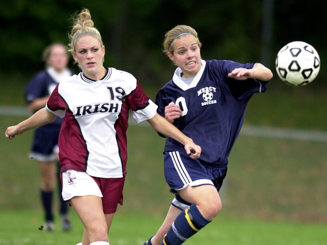 Aquinas' Rachelle Cariello, left, and Mercy's Beth Kunkel fight for possession Thursday, Oct. 17, 2002 at Aquinas High School. Kunkel scored 2 goals in Mercy's 3-1 win.