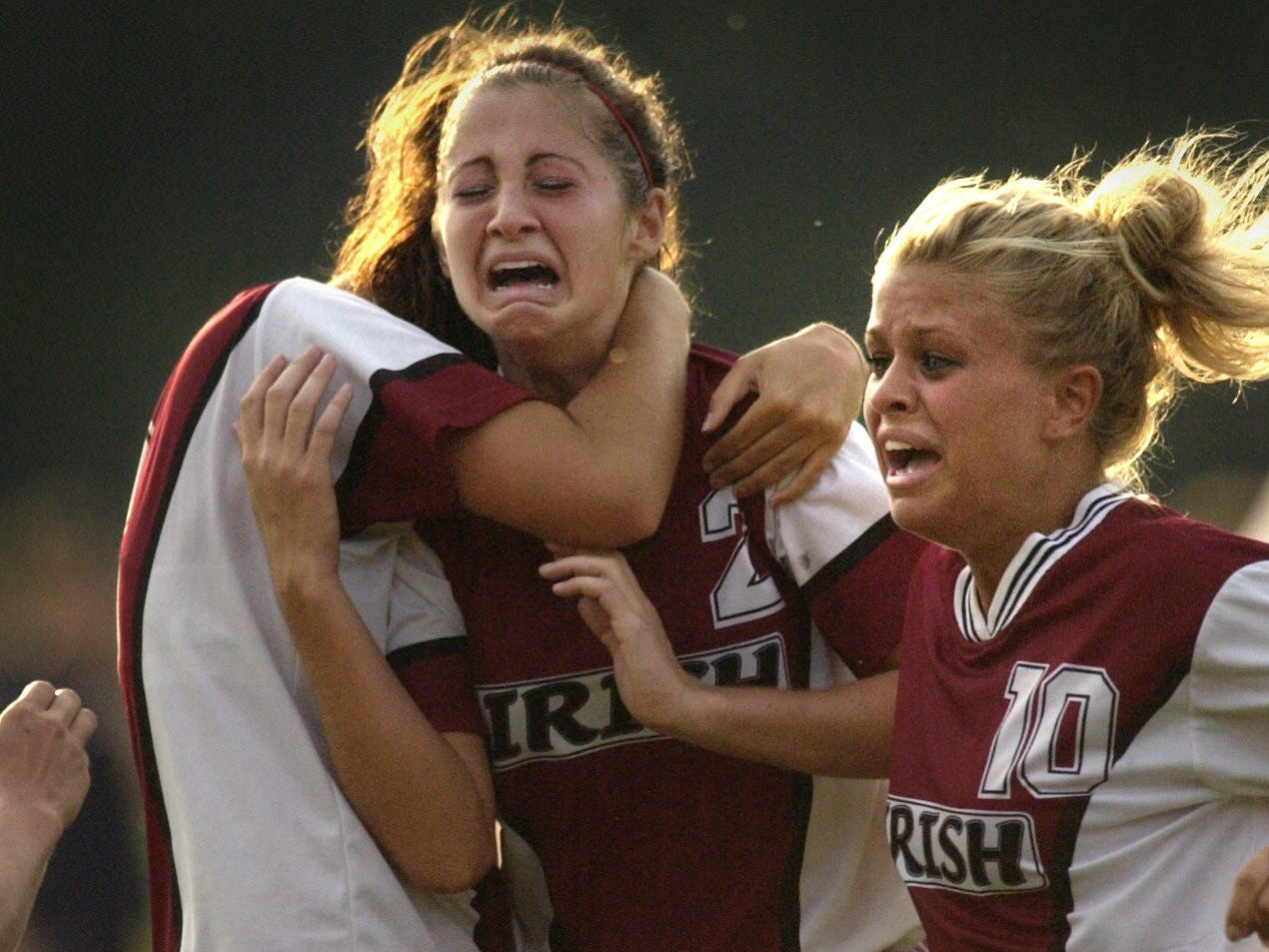 Julie Principe, center, celebrates with Aquinas teammates Carly Miller, left, and Sarah Eichas, following their 2-1 victory over rival Mercy on Sept. 14, 2004 at Mercy High School in Brighton.