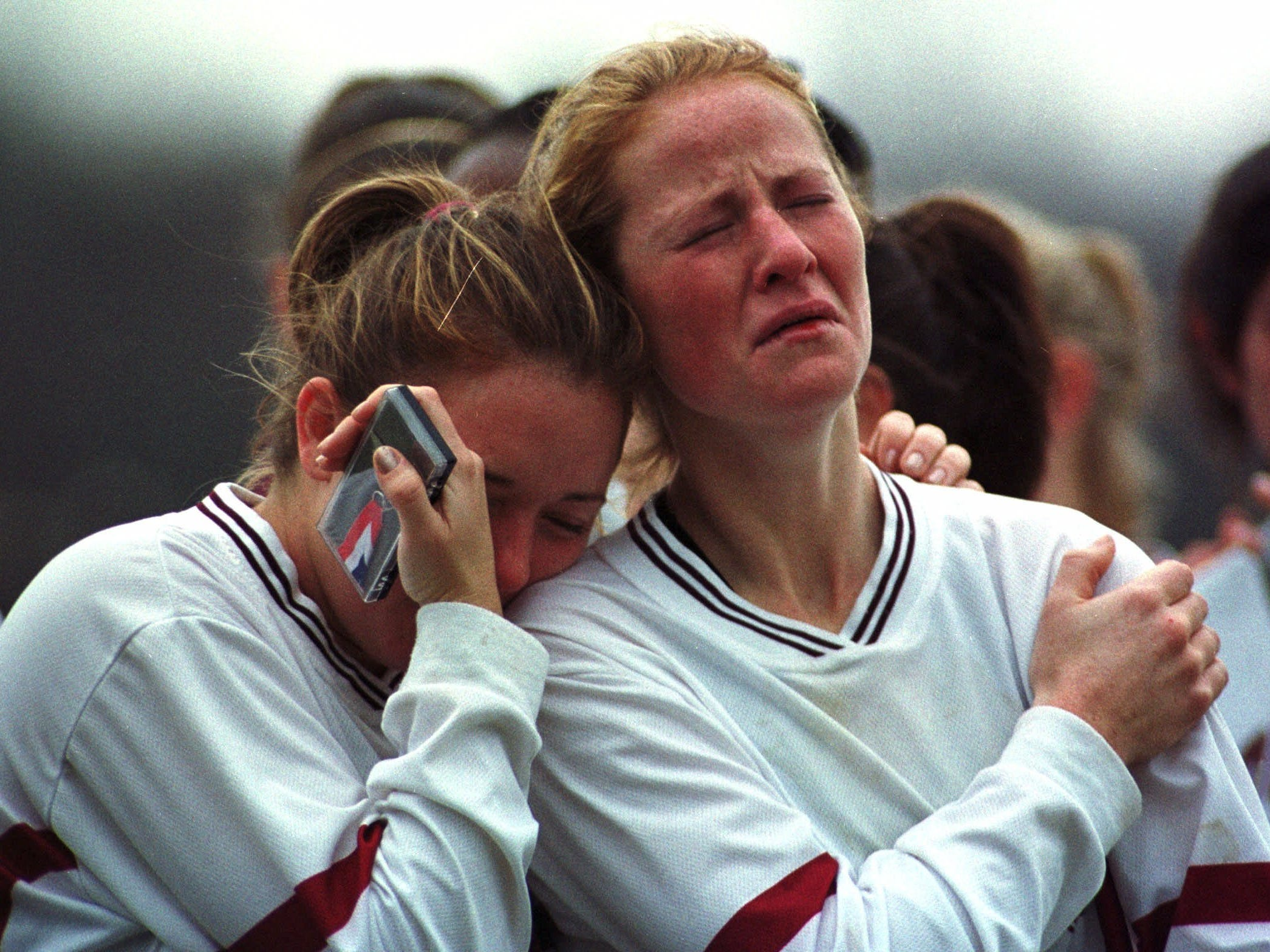 Courtney Pagani, left, leans on the shoulder of Aquinas teammate Jenica Schmidt, right, after the team's sudden death overtime loss to Westhill in the state Class B finals at Oneonta on  Nov. 20, 1999.