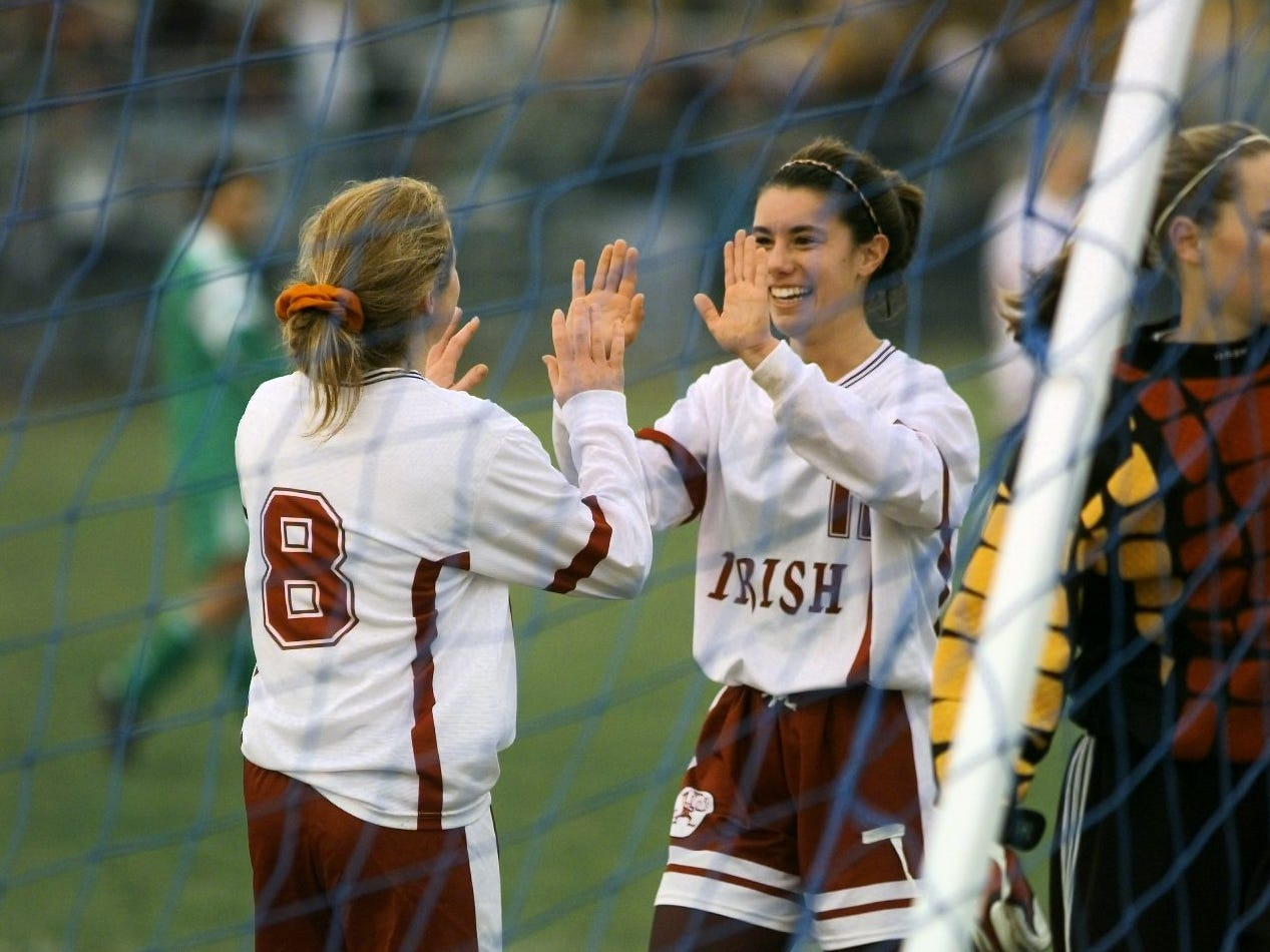 Jenica Schmidt and Lindsay Bach celebrate Bach's goal that put Aquinas ahead 5-1 in the Class B state quarterfinal game on Nov. 13, 1999 at Wheatland-Chili High School. Aquinas won the game 6-1 to advance in the state tournament.