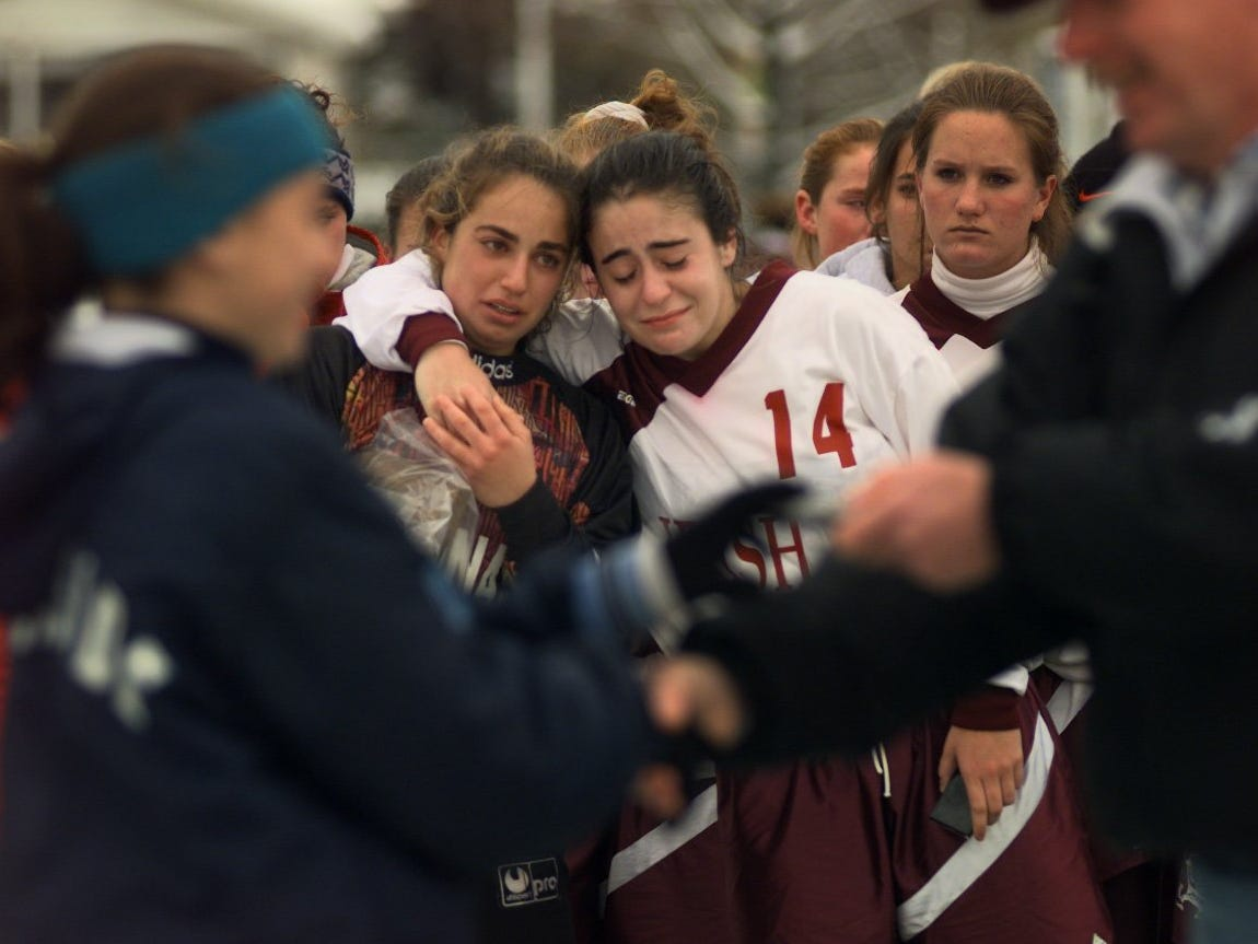Katie Gonzales, right, and Tara Berardi, of Aquinas comfort each other as players from Rockville Center Southside receive their award for winning the state championship on Nov. 15, 1997 at Hornell.