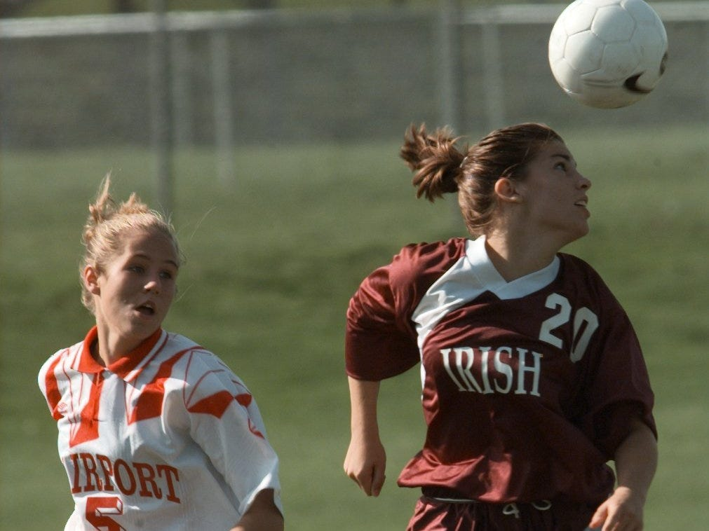 Stephanie Happ of Aquinas gets a head on the ball as Fairport's Molly Ryan defends during a game on Oct. 12, 1998.. Happ scored the only goal of the day to beat Fairport 1-0.
