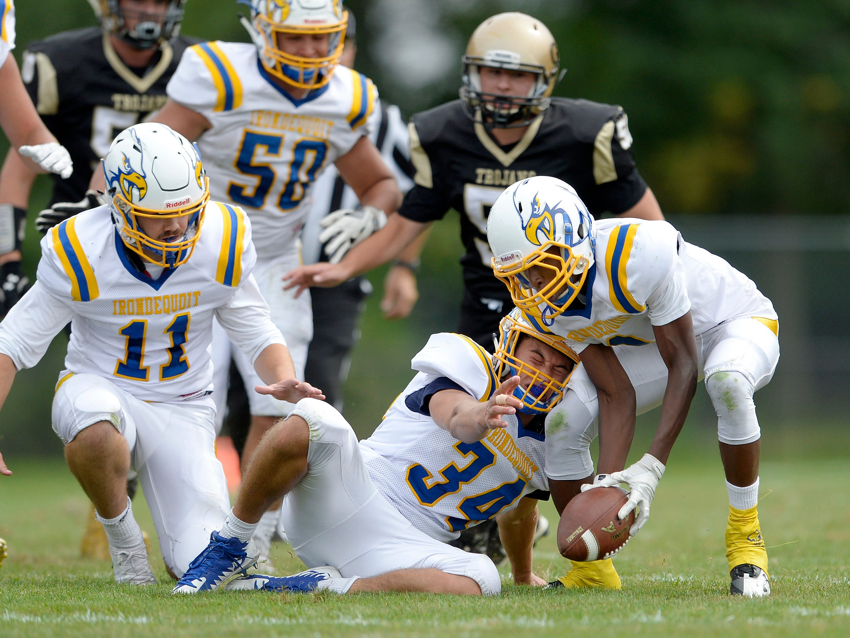 Irondequoit's JaRon Frith, right, recovers a fumble in front of teammates James Clements (34) and Liam Smith (11) on Saturday, Sept. 8, 2018. Irondequoit beat Greece Athena 42-7.