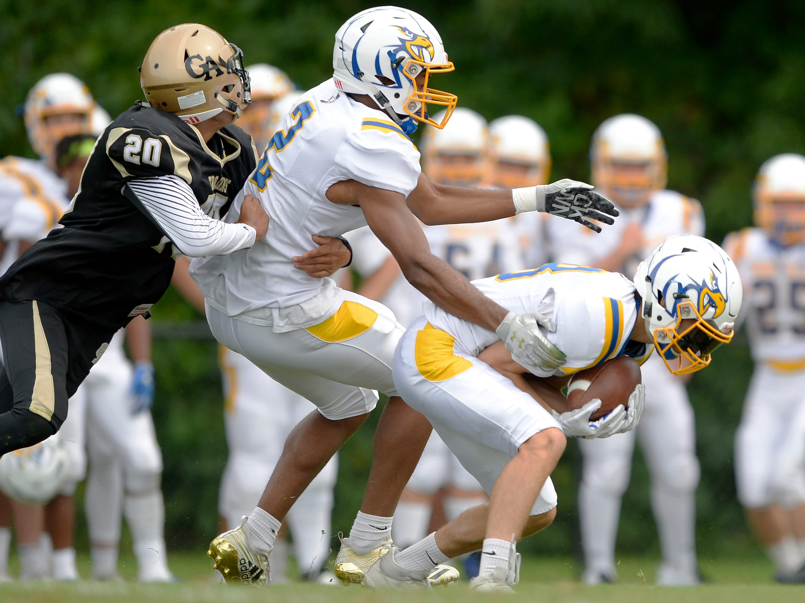 Irondequoit's Cam Kremer, right, intercepts a pass in front of Patrick Thomas IV that was intended for Greece Athena's Johnny Salone, left.