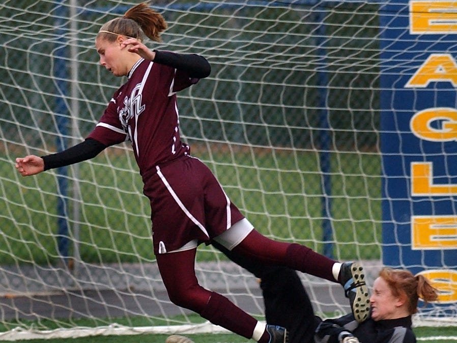 Erica Henderson of Aquinas leaps over Victor goalkeeper Kaitlin Dolan after her shot on goal and Dolan's save during a game on Nov. 5, 2005.