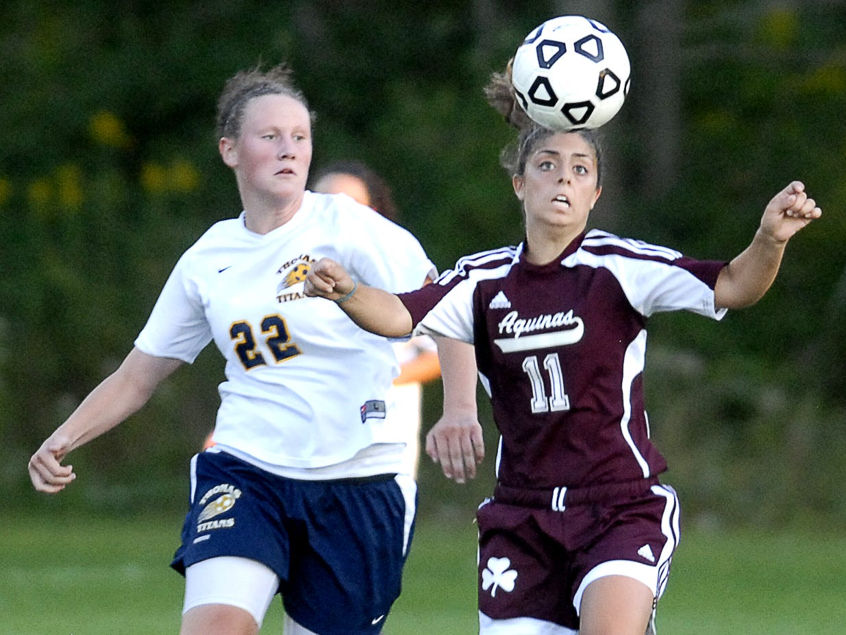 Aquinas' Briana Tata, right, heads the ball while Webster Thomas' Shannon Yokopovich defends her during the first half of the varsity girls game in Webster, on Sept. 16, 2008.
