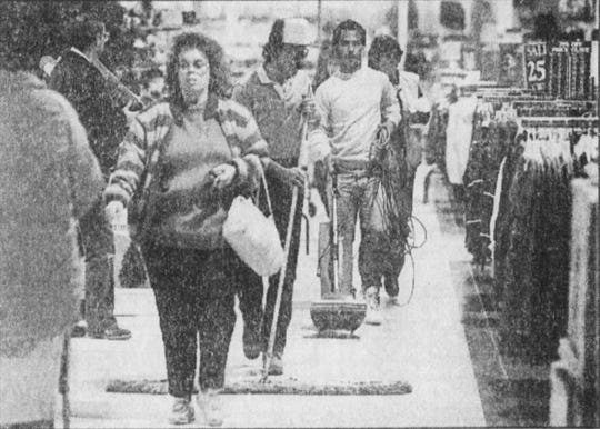 Dec. 23, ,1987: A work crew at Gold Circle cleans while shoppers explore the store during overnight shopping hours.