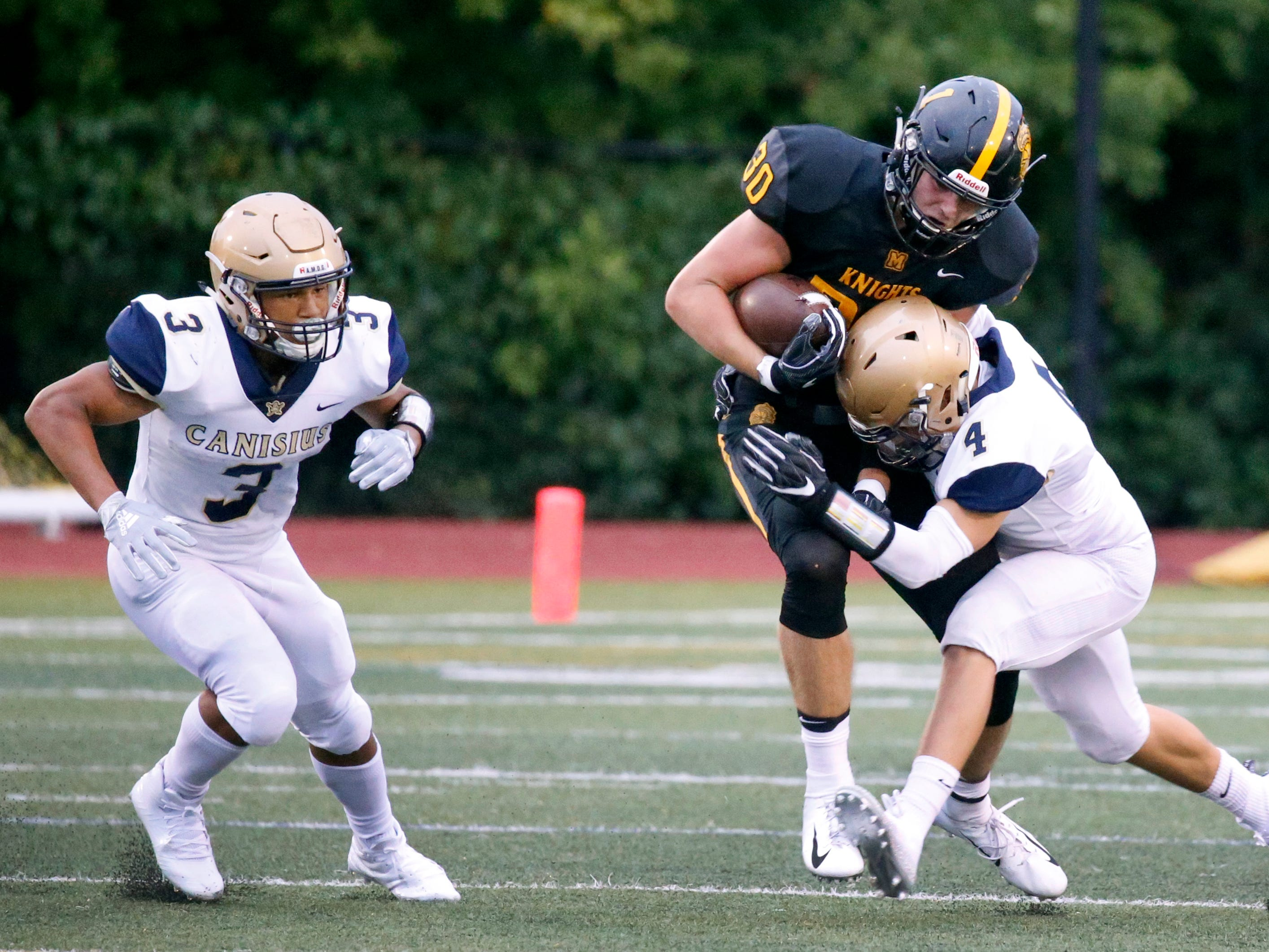 McQuaid's Connor Zamiara is tackled by Canisius' Nathan Drilling in the first quarter at McQuaid Jesuit High School.