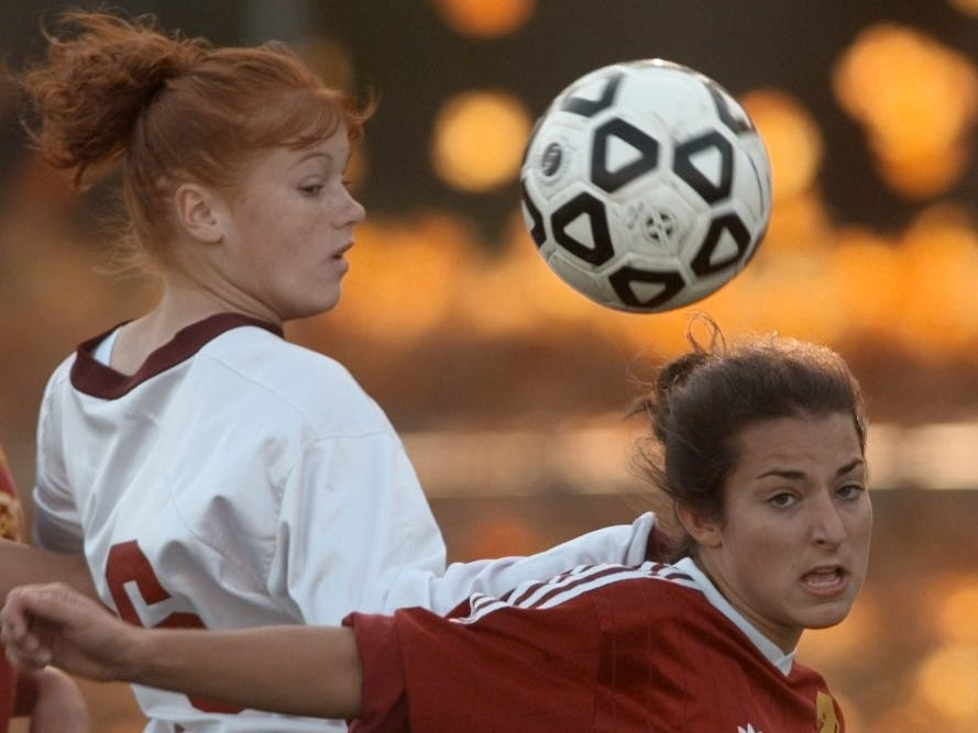 Aquinas' forward Katie Loomis, left, and Pittsford Mendon defender Caitlin Kummer fight for possession of the ball during a game on Oct. 16, 1998.