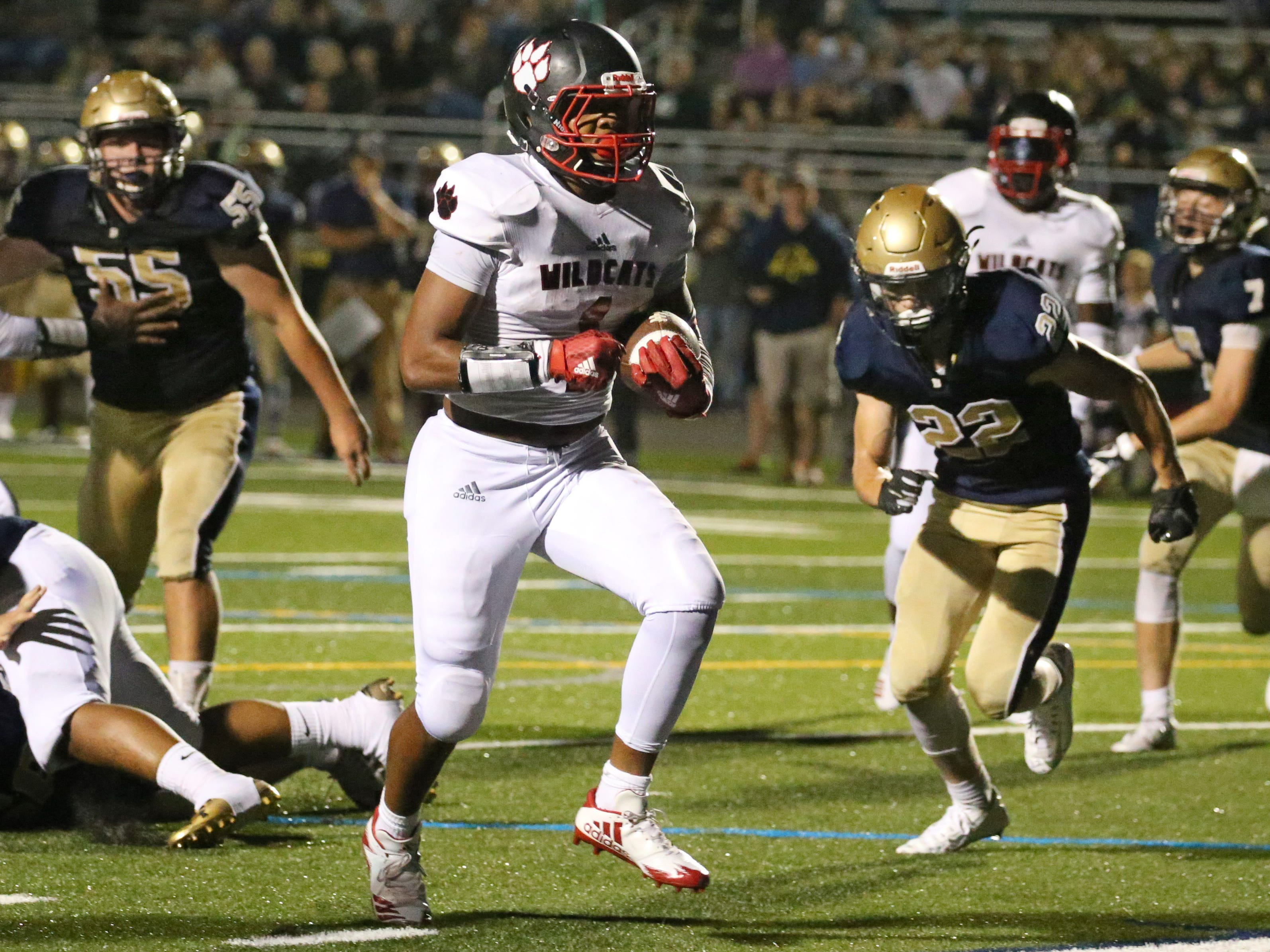 Wilson's Desi Floyd Jr., center, races through a big hole in the line to score in the second quarter.