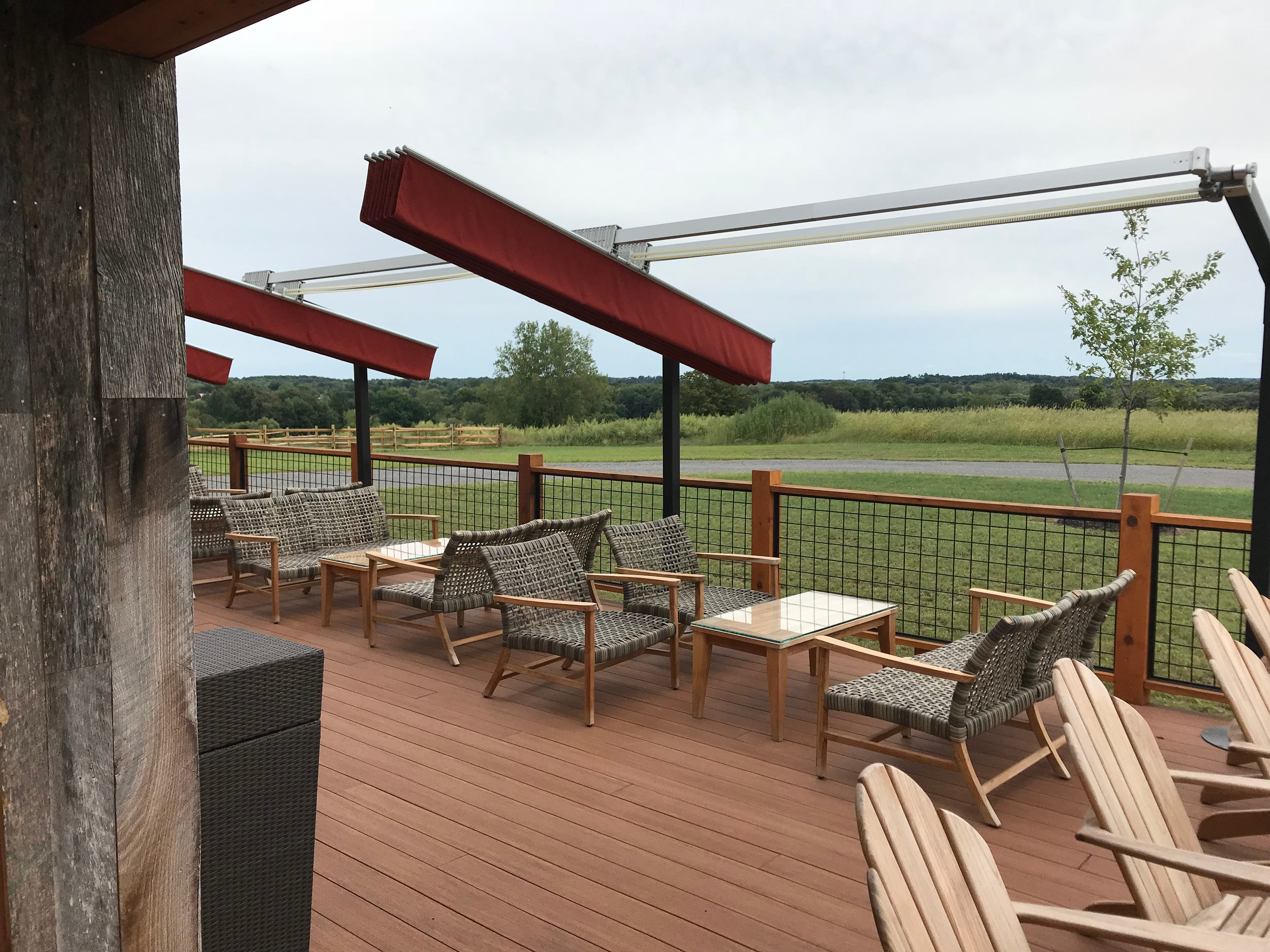Outdoor seating options, underneath retractable umbrellas, at Oak & Apple Cidery in Penfield.