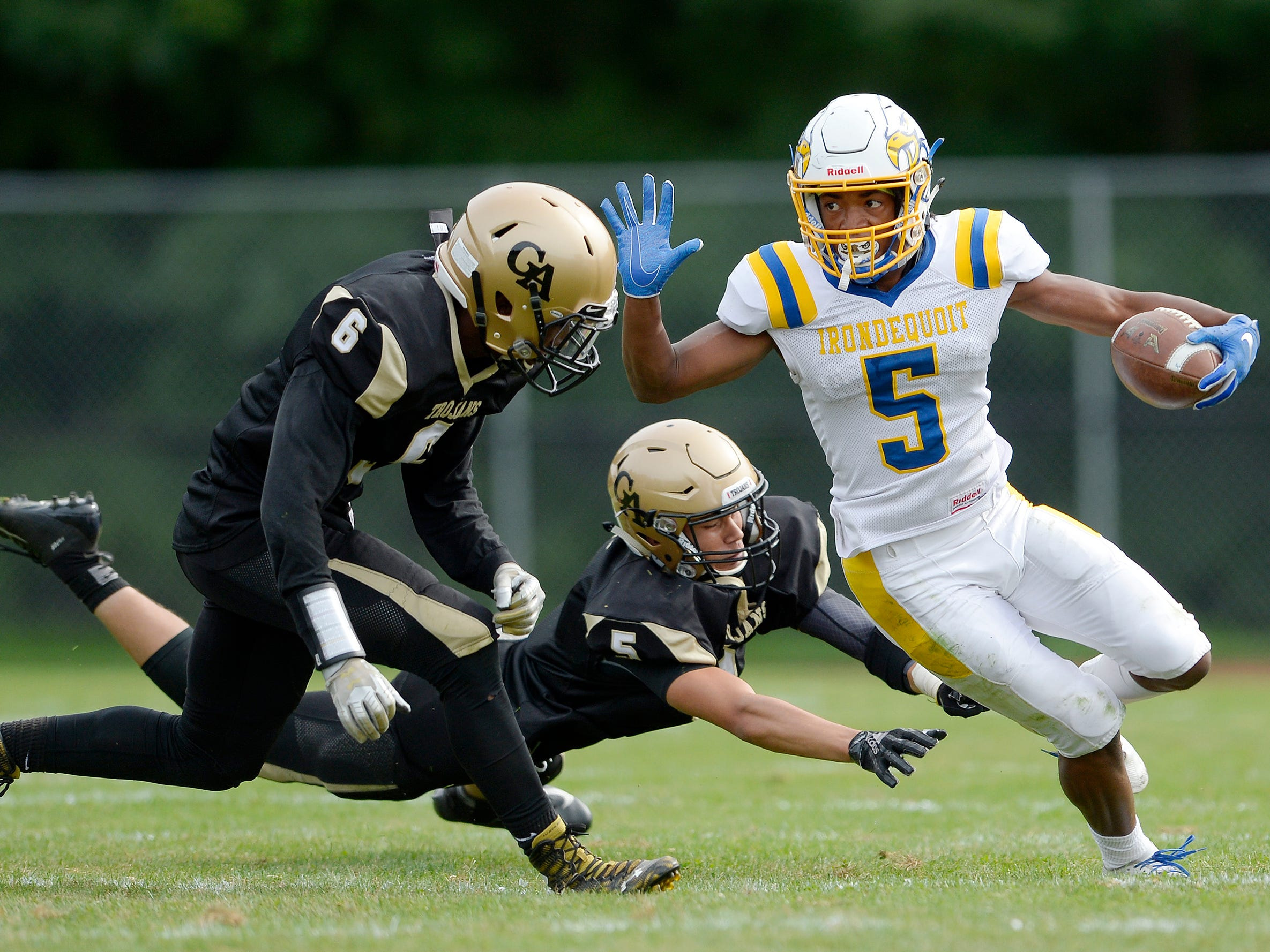 Irondequoit's Jadon Turner, right, eludes the tackles of Greece Athena's Nate Bogoniewski, bottom, and Kelvin Reaves during a regular season game played at Greece Athena High School, Saturday, Sept. 8, 2018. Irondequoit beat Greece Athena 42-7.