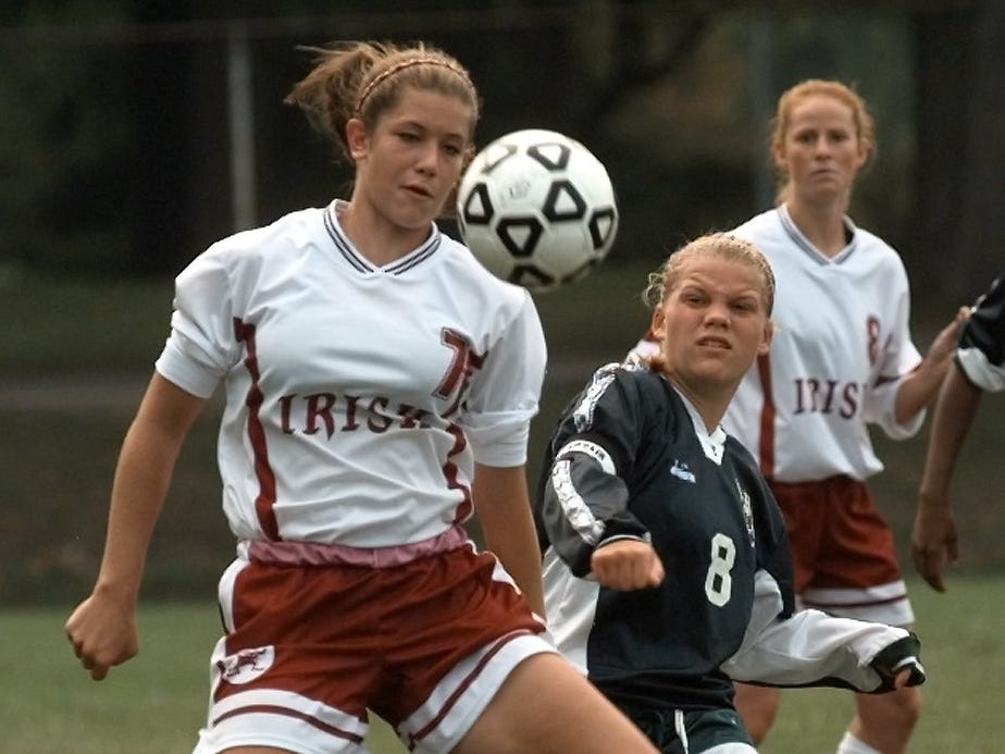 Aquinas's Lauren Mort knees the ball from Rush-Henrietta's Jody Alvarez during the second half of their game, Sept. 8, 1999.