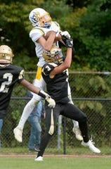 Irondequoit's Quinn Simenson catches a touchdown pass over Greece Athena's Sam Sheldon.