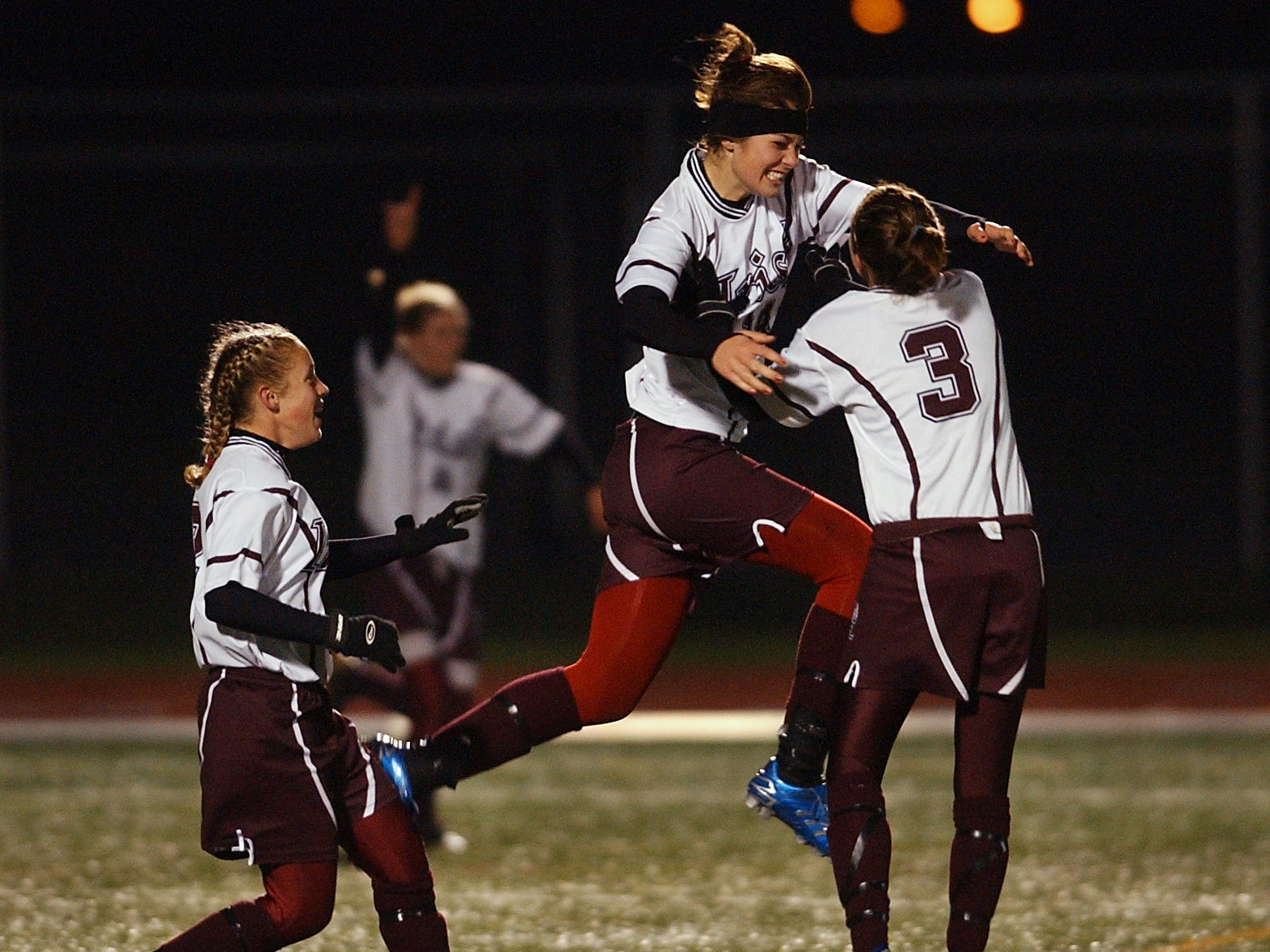 Aquinas Ashley Hughes, left, watches Olivia Guy jump with excitement towards Ashley Grove after Guy scored the third goal for Aquinas in a 3-1 overtime win against Union Endicott on Nov. 17, 2006.