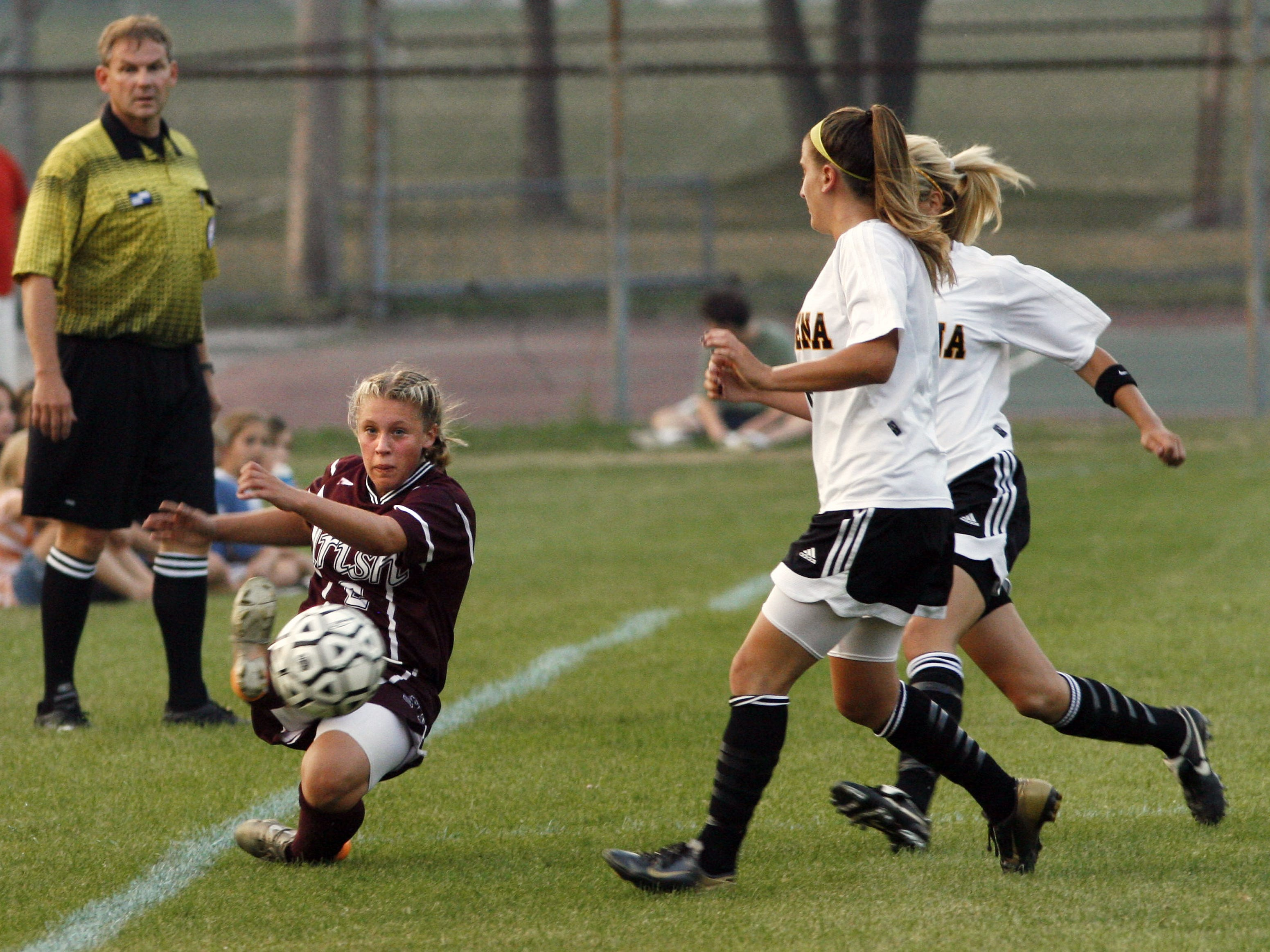 Aquinas' Ashley Hughes, left, makes a sliding play to keep the ball in bounds as Greece Athena players close in on Sept. 6, 2007.