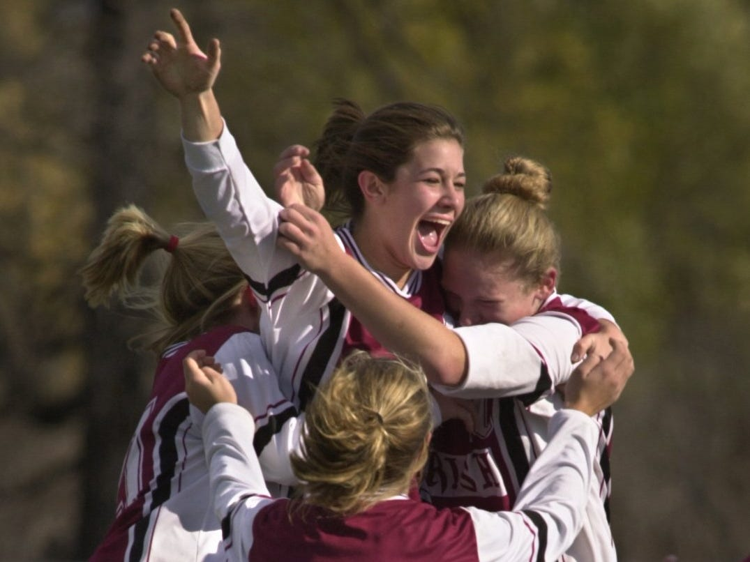 Aquinas' Lauren Mort is surrounded by her teammates after she scored the game's only goal midway through the first half Saturday at Webster High School on Nov. 18, 2000. Aquinas defeated Oneonta to claim the state Class B girls soccer championship. The championship started a run of three straight state titles for Aquinas.