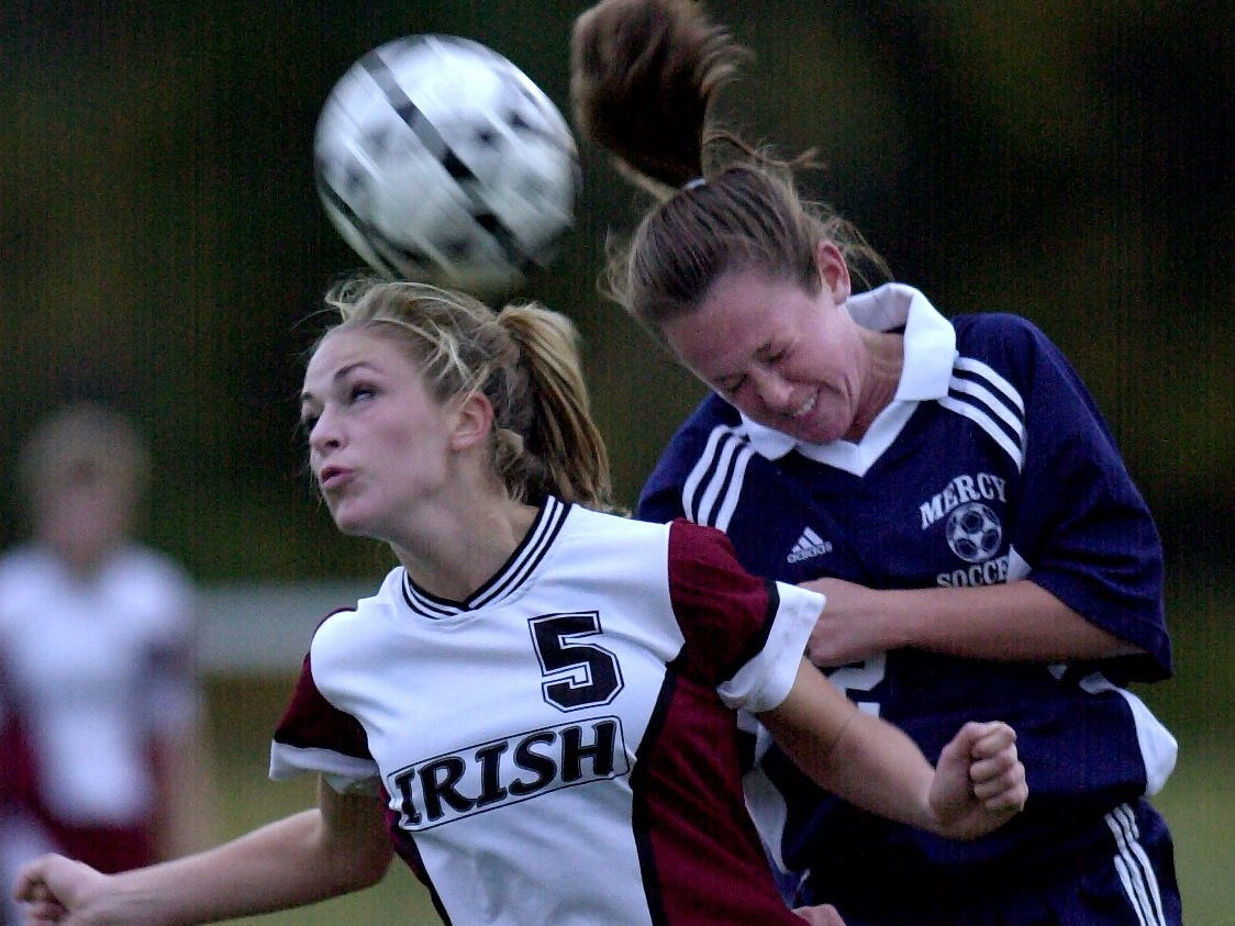 Rachelle Cariello of Aquinas, left, and Kathleen Martin of Mercy battle for the ball in overtime of a game on Oct. 16, 2003.