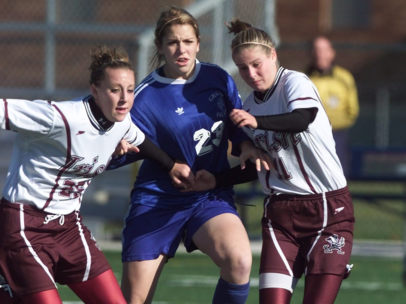 Grand Island's Sarah Sukmanowski is sandwiched between Aquinas' Meaghan Magee, left, and Erica Henderson during a state Class A playoff game on Nov. 12, 2005.