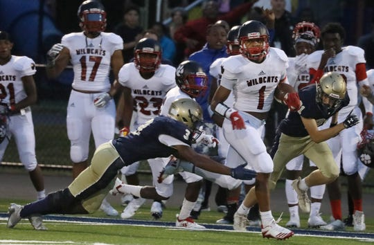 Wilson's Desi Floyd Jr., right, races down the sideline, away from a diving Brighton's Demond McFarland, to score on the Wildcats opening possession of the first quarter.