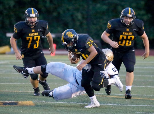 McQuaid's Mark Passero is tackled by Canisius' Donovan Cornelius in the first quarter at McQuaid Jesuit High School.