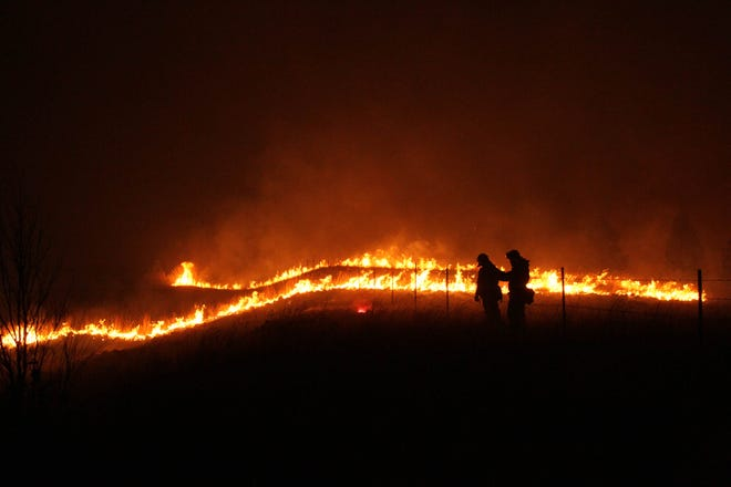 Firefighters are shown standing guard along I-5 north of the Pollard Flat exit as the Delta Fire flares up in the background on Sept. 7, 2018. (Hung T. Vu/Special to the Record Searchlight)